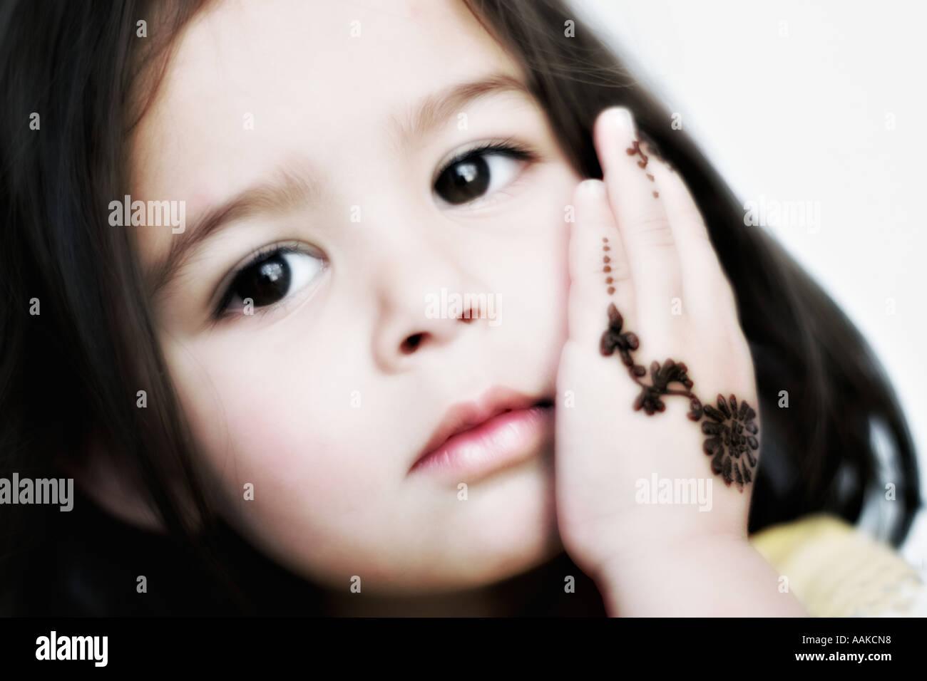 Zwei Jahre altes Mädchen mit großen braunen Augen und Henna auf ihre ...