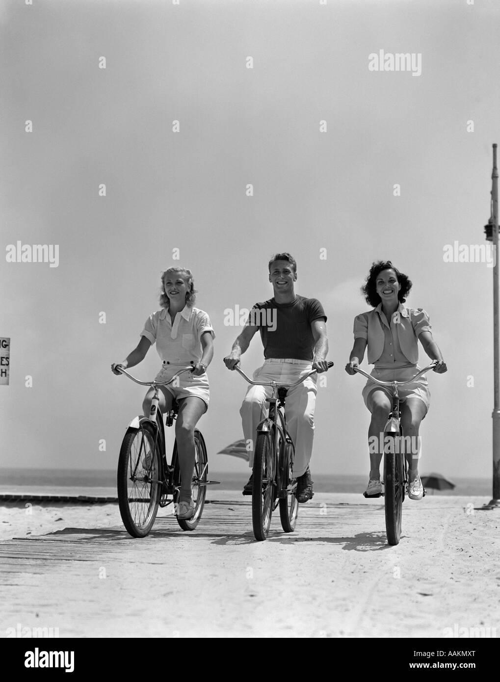 1940ER JAHRE MANN ZWEI FRAUEN BIKE-STRANDPROMENADE Stockfoto