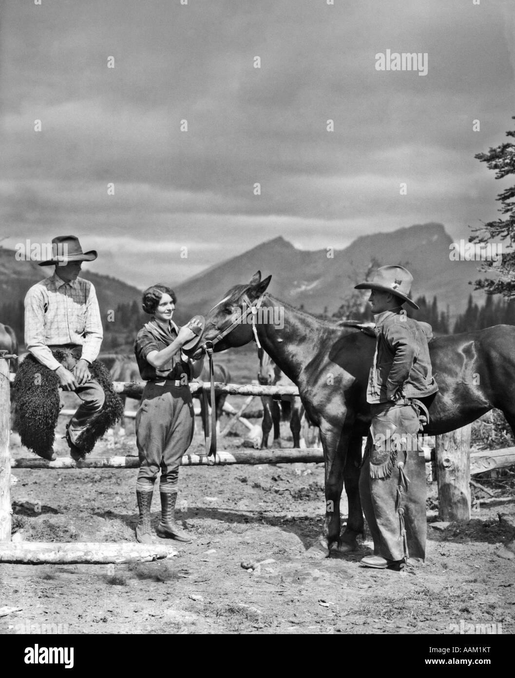 1930ER JAHREN ZWEI COWBOYS & EINE FRAU, DIE PFLEGEND EIN PFERD IN DER NÄHE VON DER KOPPEL STEHEN COWBOY IST TRAGEN Stockfoto