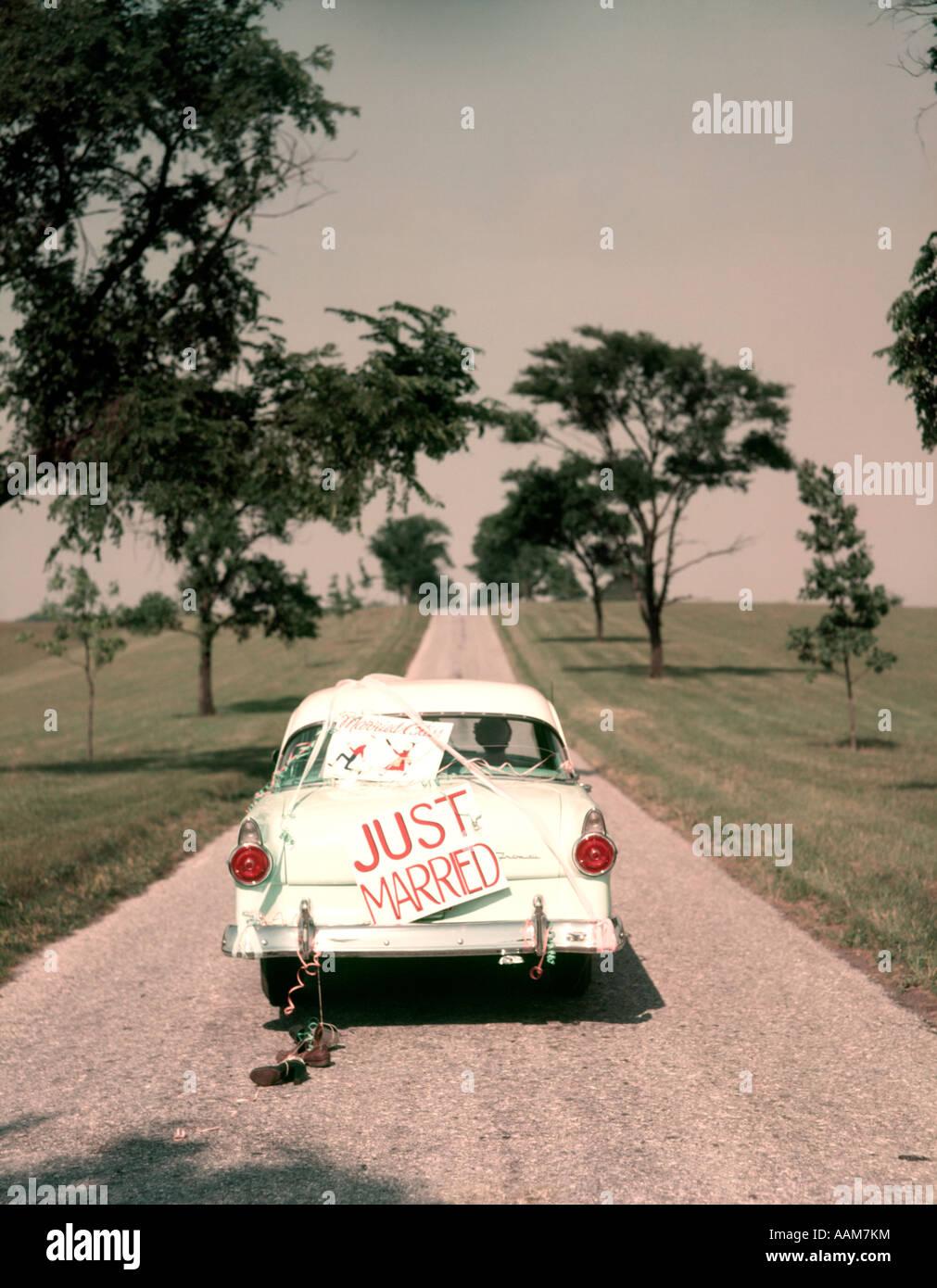 1950ER JAHREN PAAR BRAUT UND BRÄUTIGAM REITEN IN FORD SEDAN AM BEGINN DES LANGEN WEGES NUR VERHEIRATET SCHILD Stockbild