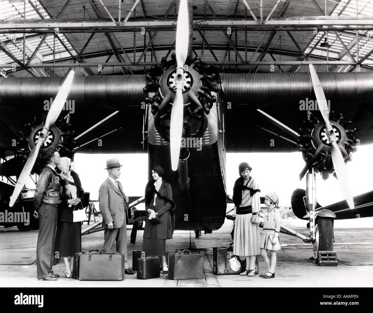 1920S 1930S GRUPPE PASSAGIERE WARTEN VOR DER FORD TRI-MOTOR FLUGZEUG Stockfoto