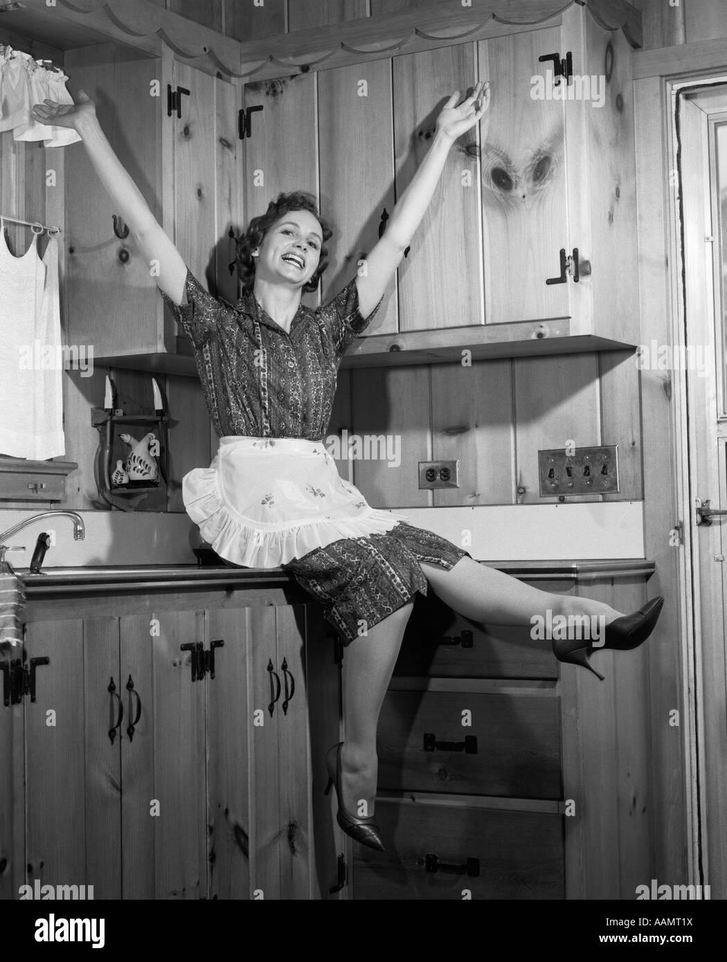 1950er jahre hausfrau sitzen auf arbeitsplatte treten f e arme in die luft stockfoto bild. Black Bedroom Furniture Sets. Home Design Ideas
