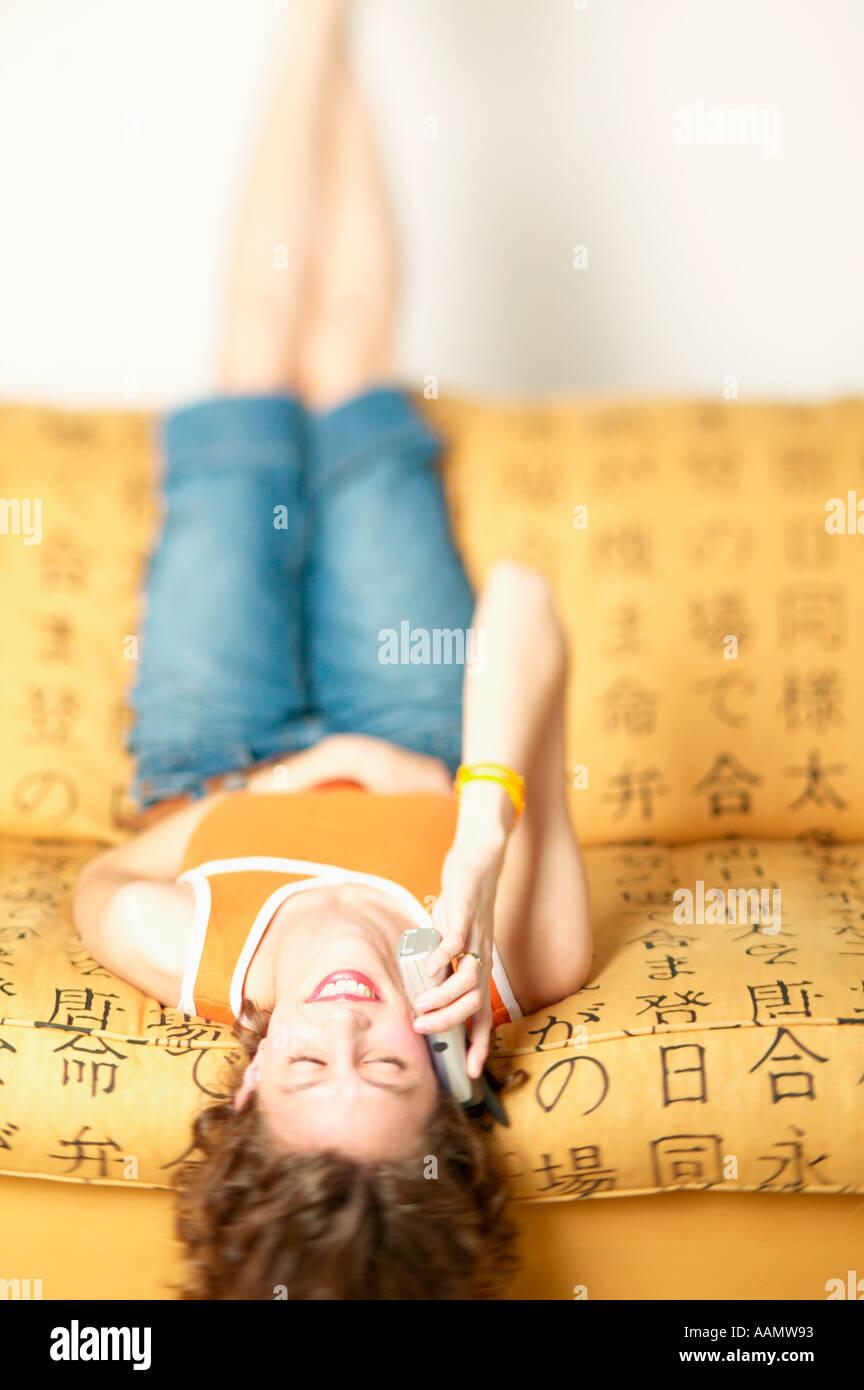 Frau am Handy während der Verlegung auf den Kopf gestellt Stockfoto