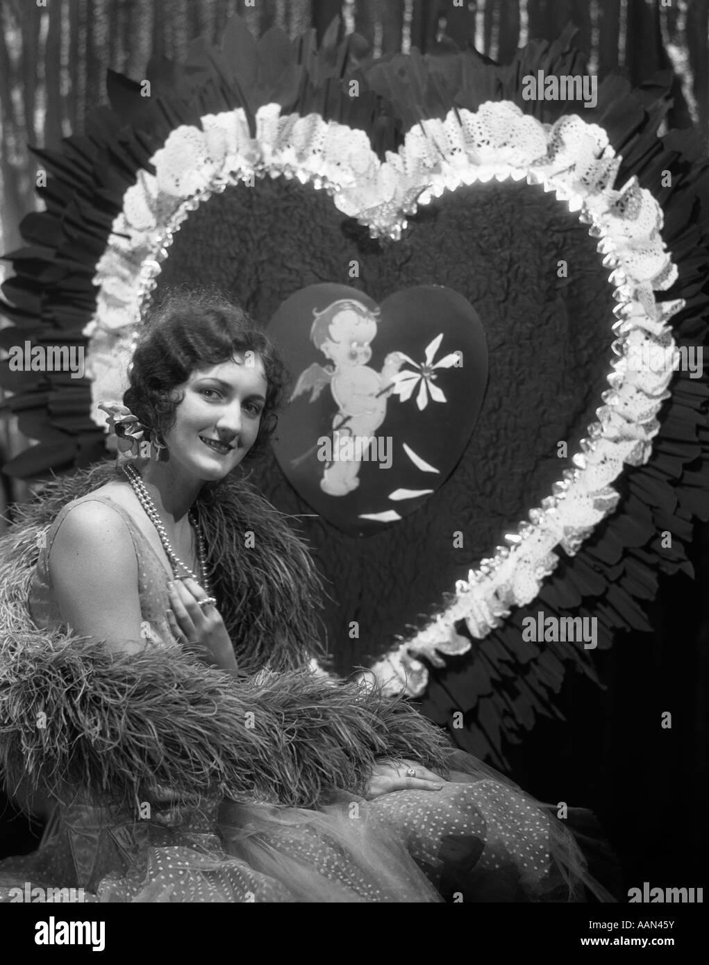 1920S 1930S LÄCHELNDE JUNGE FRAU KAMERA FINGER WAVE HAAR PERLEN FEDERBOA RIESEN VALENTINE HERZEN BETRACHTEN Stockbild