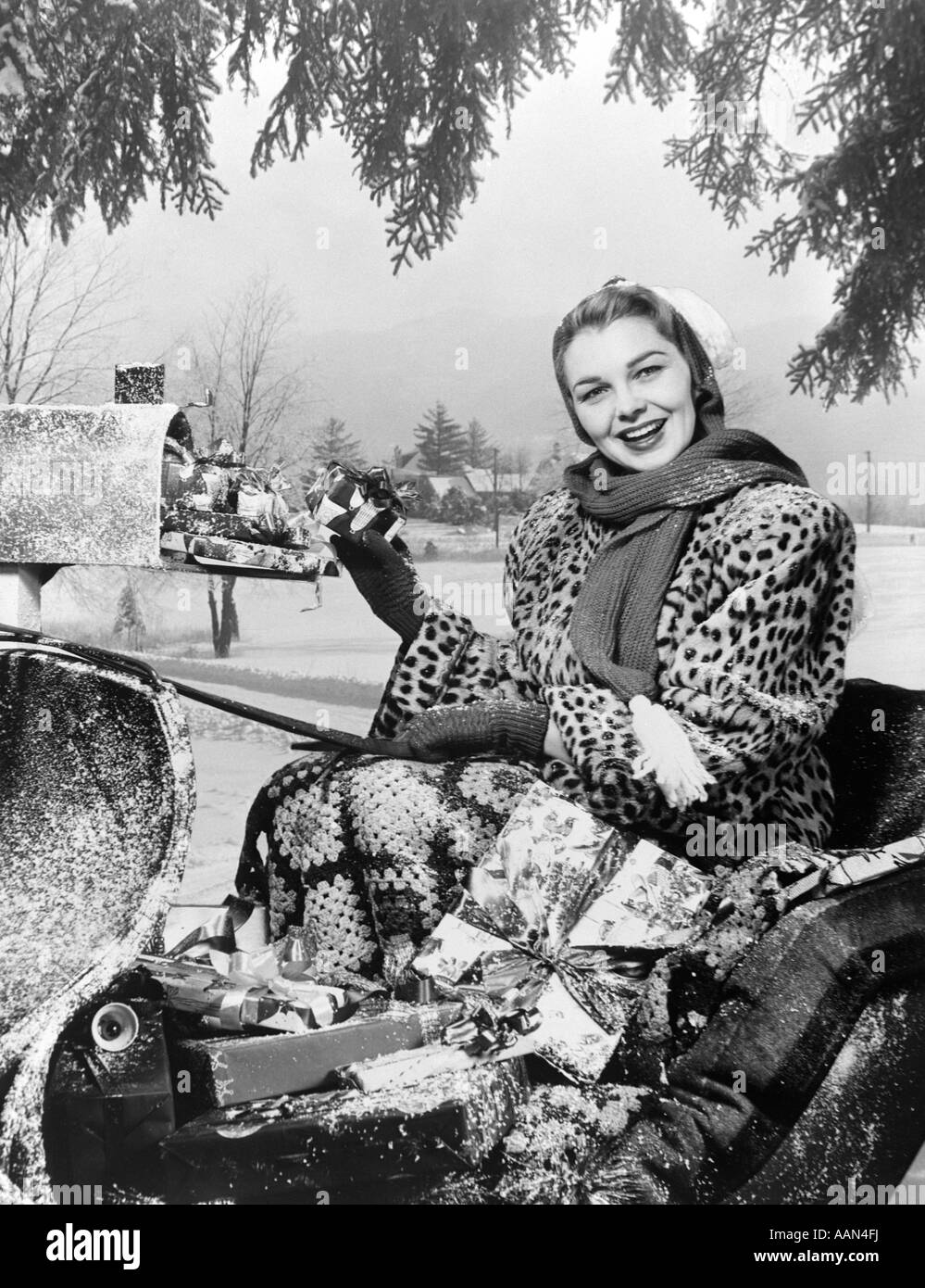1950ER JAHREN LÄCHELNDE FRAU BLICK IN DIE KAMERA REITEN IN SCHLITTEN TRAGEN LEOPARD HAUT PELZMANTEL IN MAILBOX Stockbild