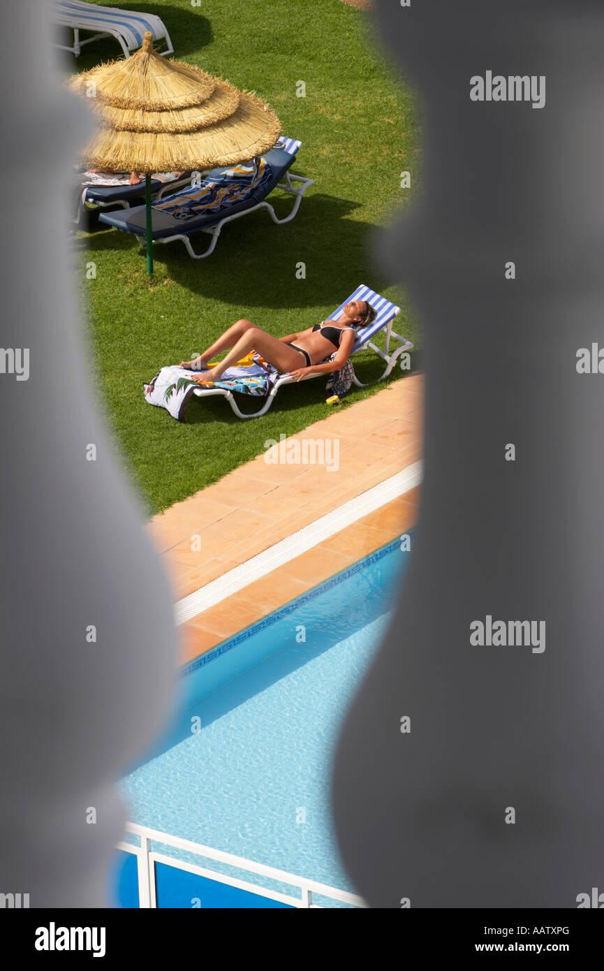 vertikale heimlich Blick durch Balkon hinunter auf ahnungslose Sonnenbaden Frau am Pool auf dem Gelände eines Stockbild