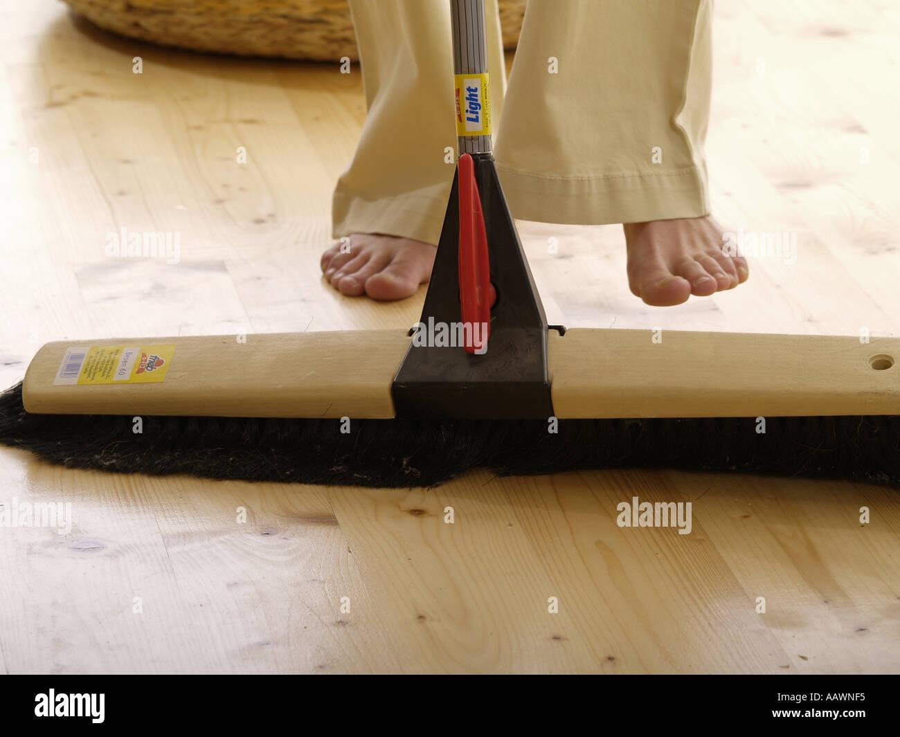 Holzfußboden Reinigen ~ Junge frau teenager füße auf dem holzboden mit einem besen reinigen