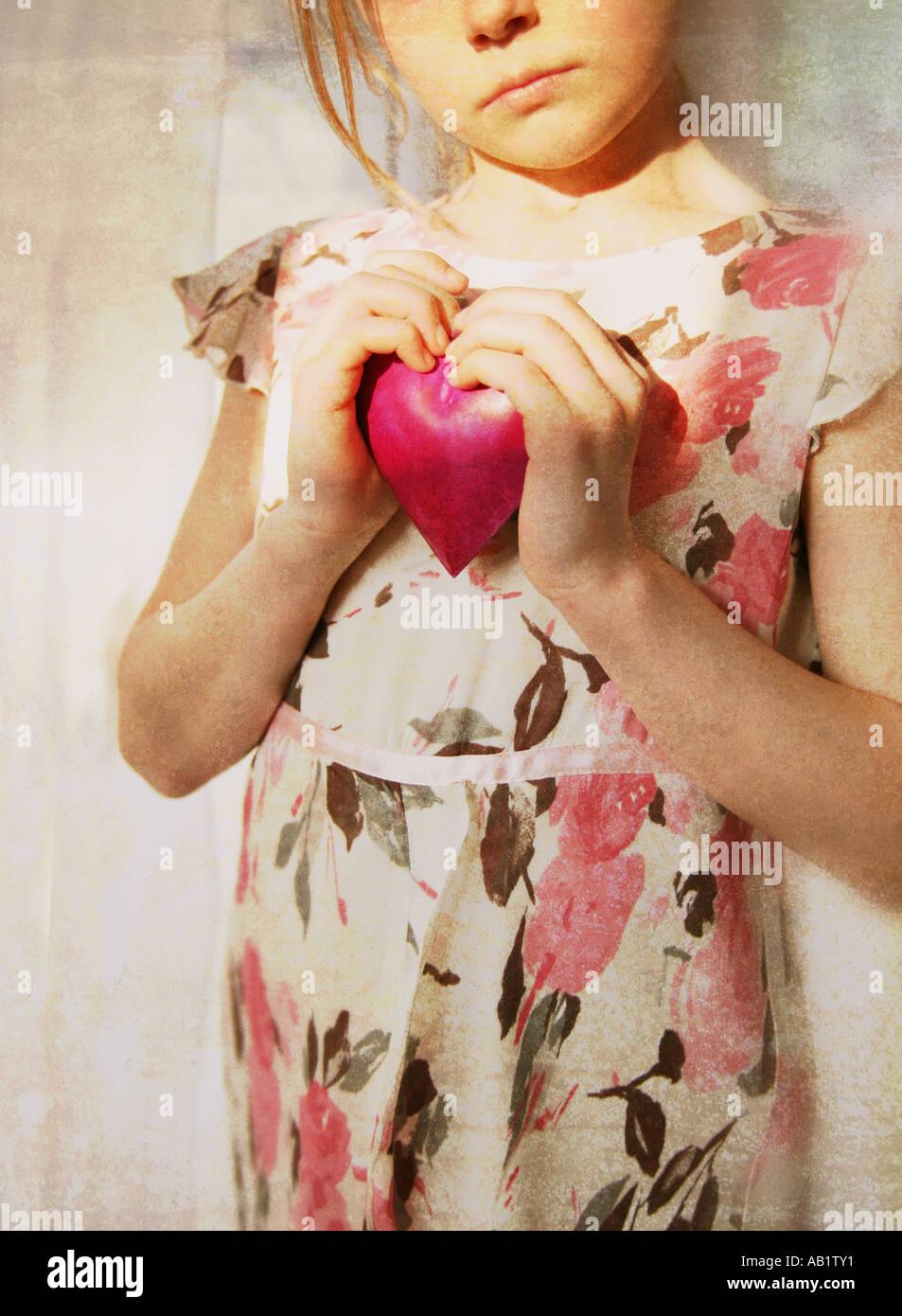 ein Mädchen hält ein rosa Herz Stockbild