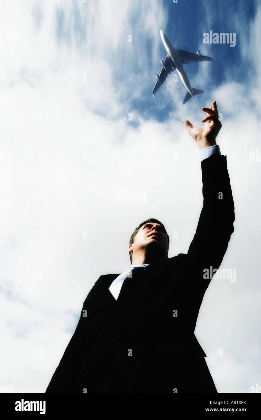 ein Geschäftsmann, der vorgibt, ein Flugzeug zu werfen Stockbild