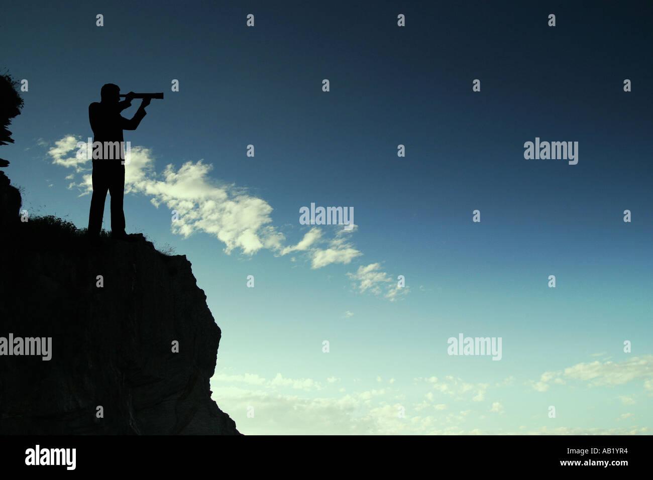 ein Mann auf einer Klippe mit einem Teleskop Stockbild