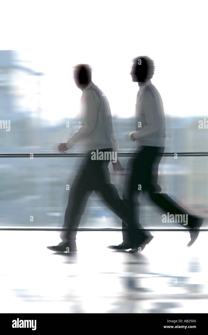 2 Manager laufen vor einem großen Fenster 2 Manager Im Hemd Laufen Vor Einem Großen Fenster Stockbild
