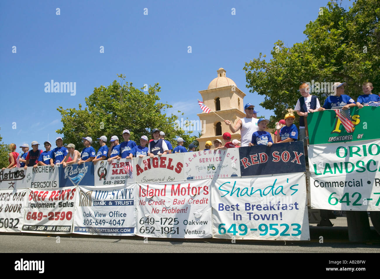 Float von ein Little League Baseball-Teams mit Sponsorenwerbung bahnt sich ihren Weg durch Hauptstraße während Stockbild