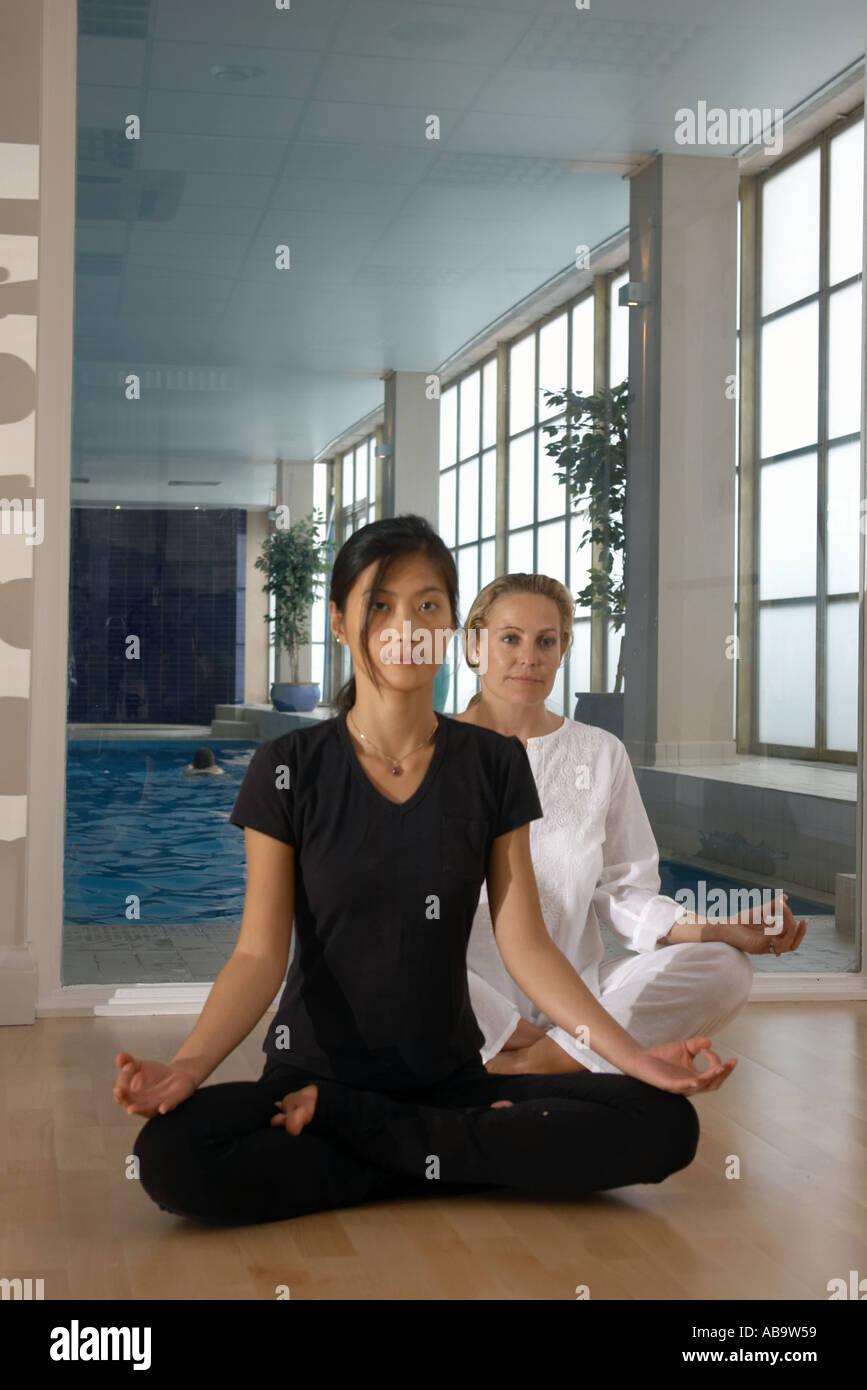 zwei Frauen zwanziger dreißiger Jahre in Yogaposition Stockbild