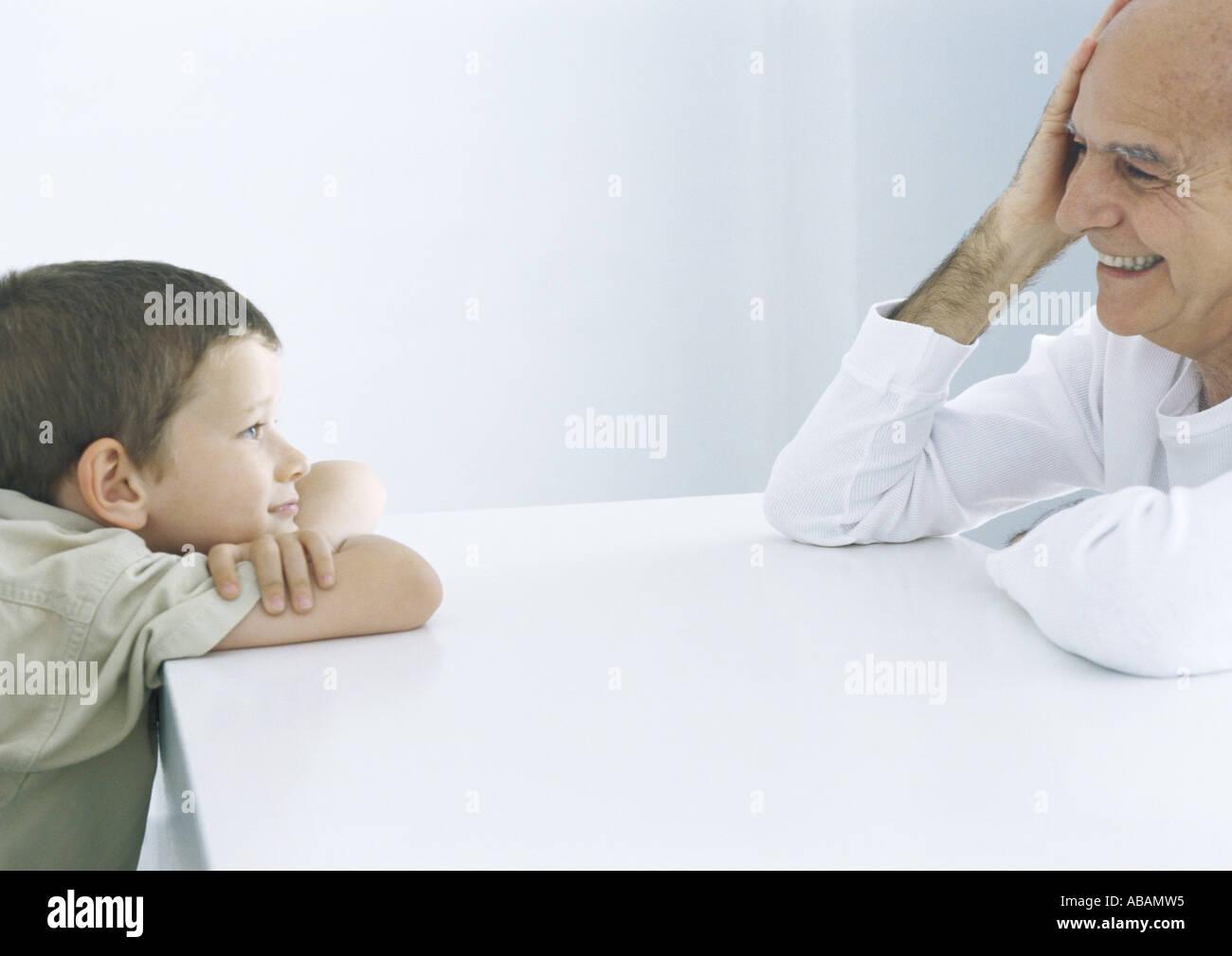 Junge und Großvater sitzen über Tisch, Lächeln einander an Stockbild