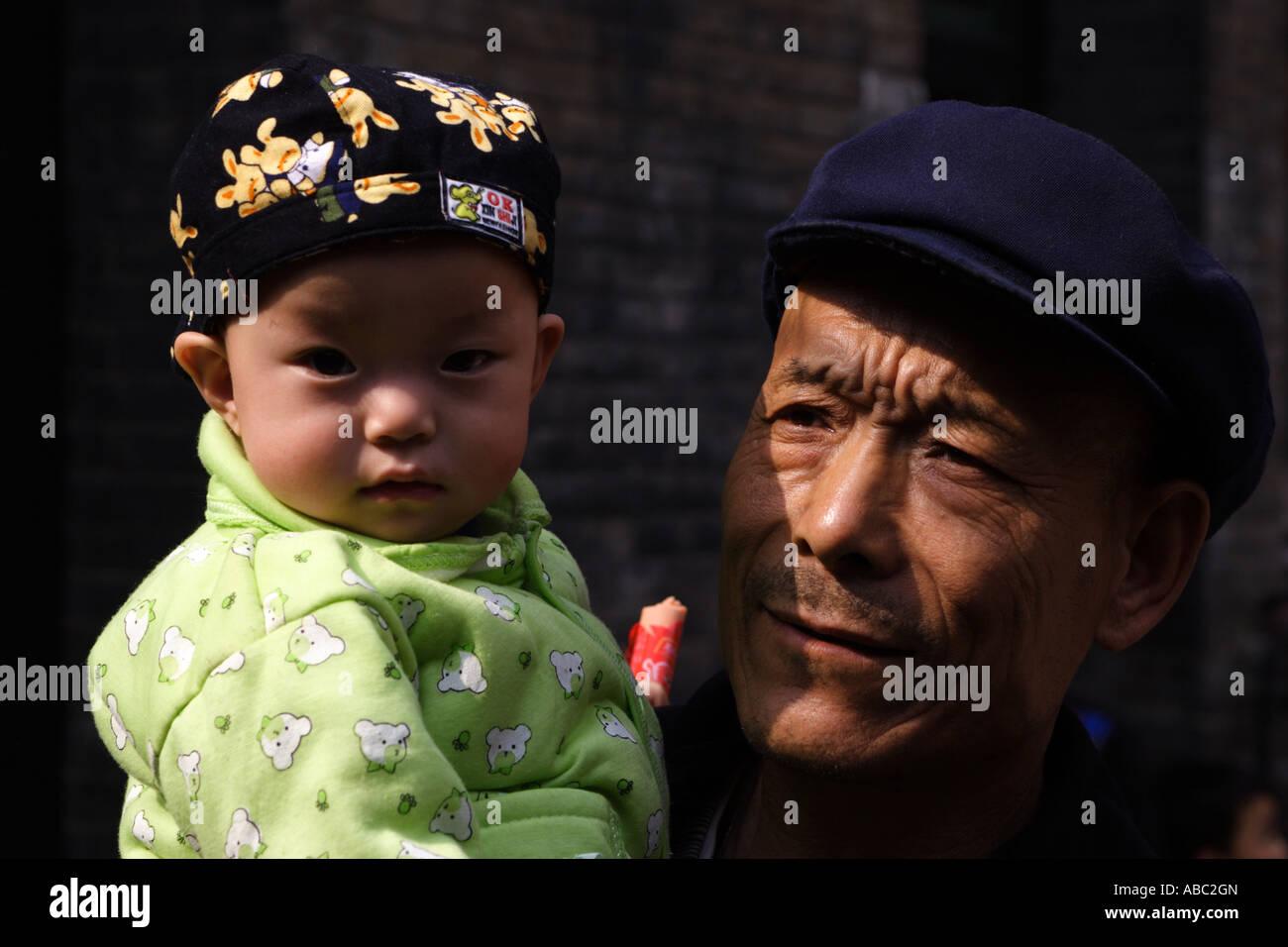 Über die Generationen hinweg. Ein chinesischer Mann hält ein Kind in Silber-Dollar-Dorf, Shanxi Provinz, Stockbild