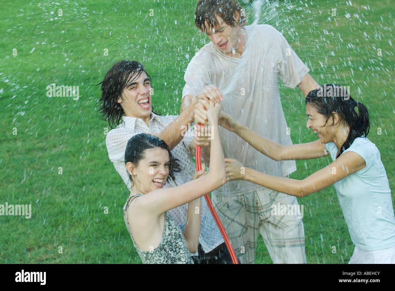 Gruppe junger Freunde spielen mit Gartenschlauch, nass Stockbild
