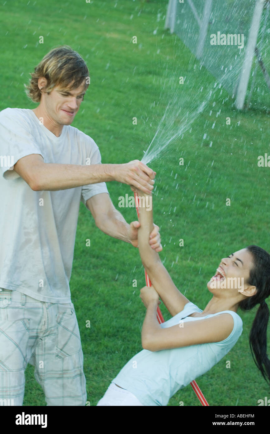 Junge Freunde spielen mit Gartenschlauch, nass Stockbild