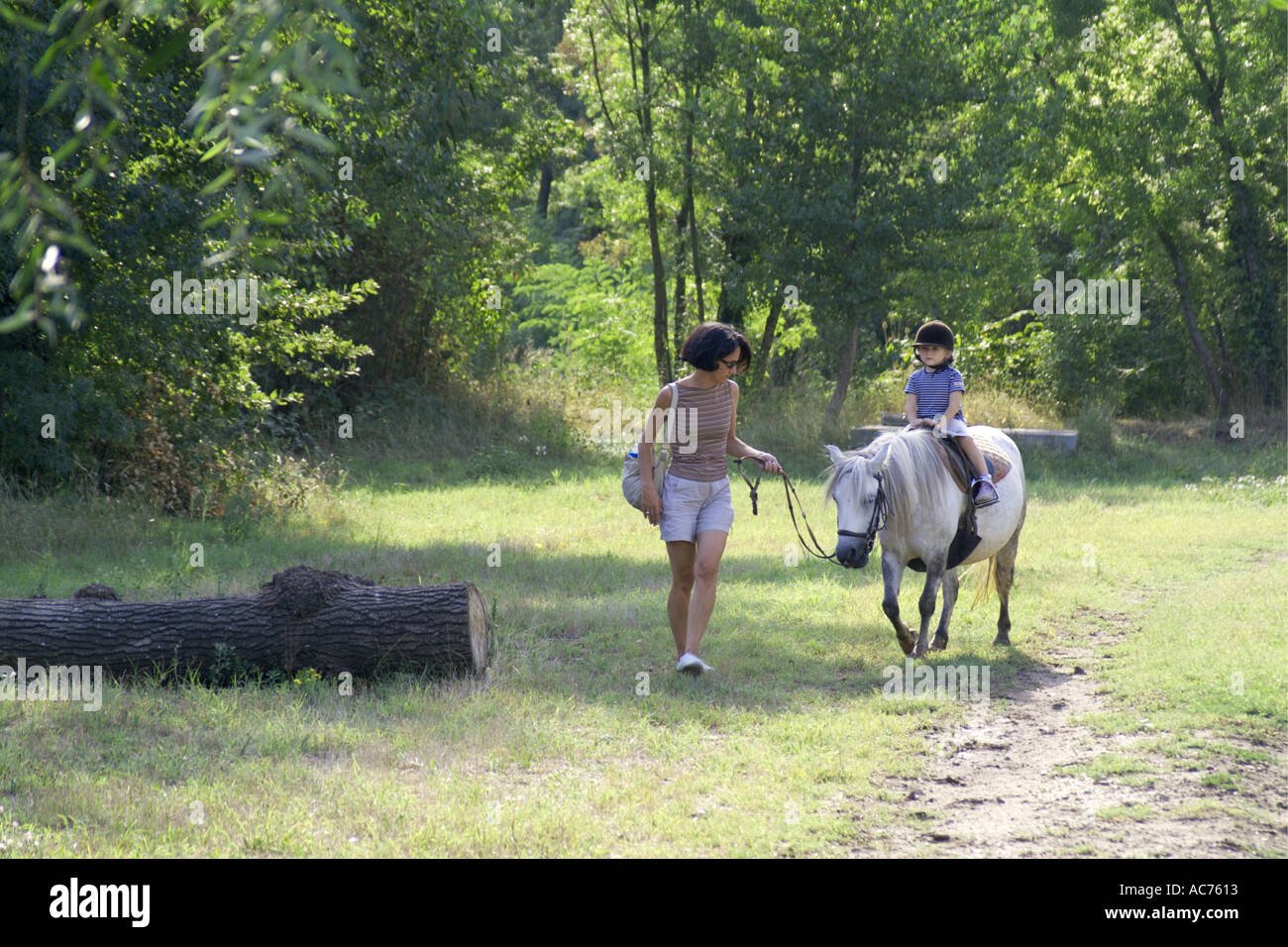 Mutter führt junge Tochter auf einem Pony Frankreich Stockbild