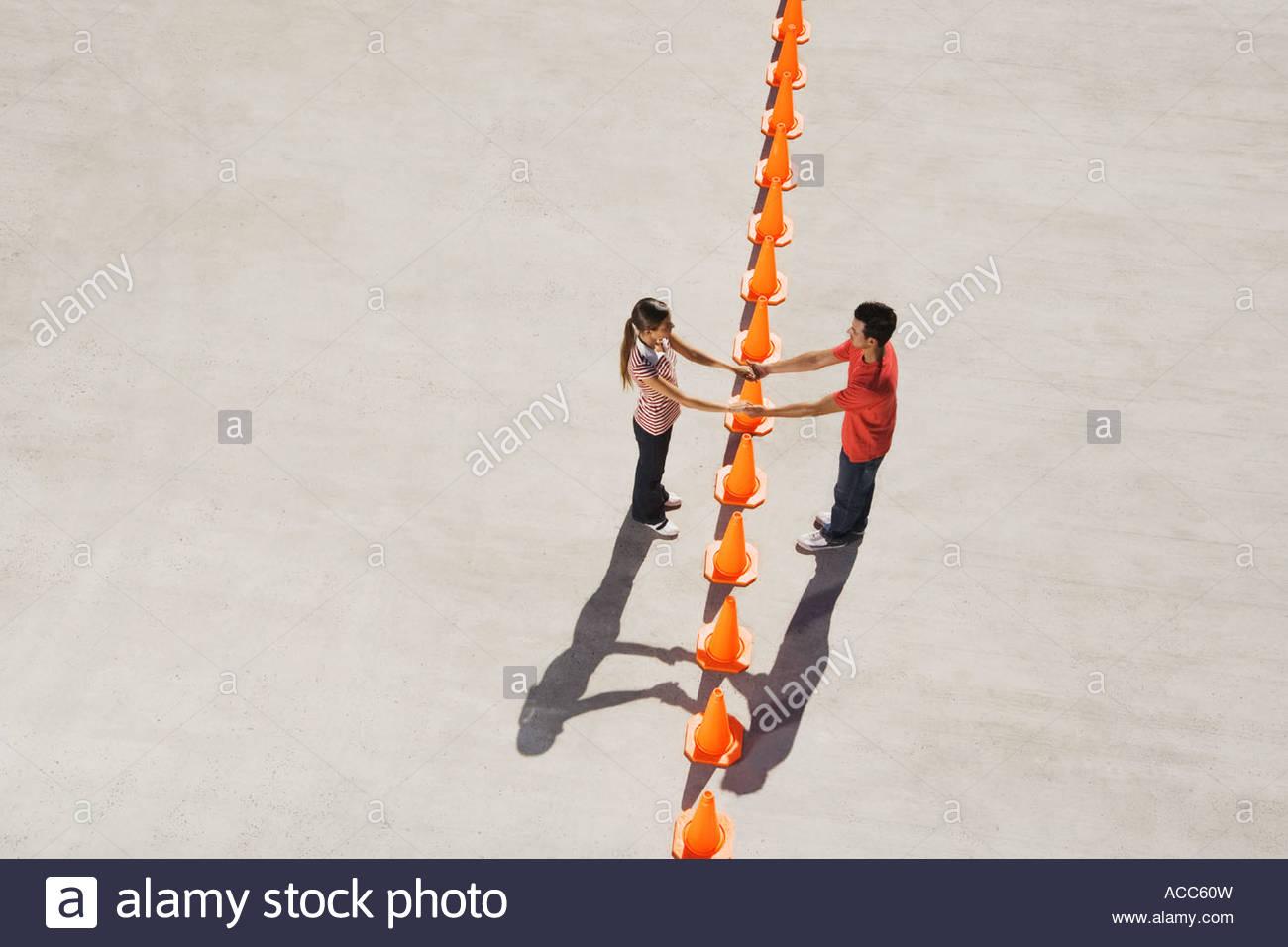 Mann und Frau, die Hand in Hand über Reihe der Leitkegel Stockbild