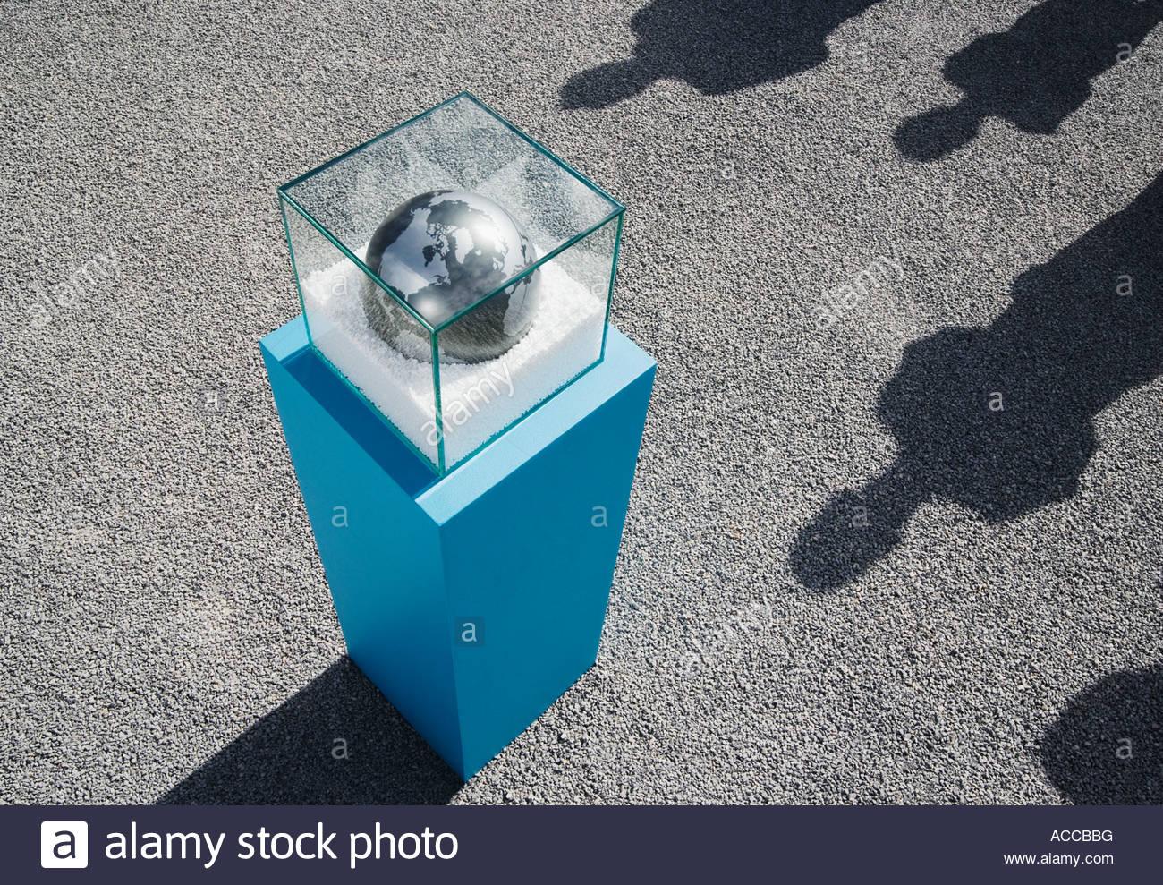 Globus im Glaskasten auf Sockel mit vier langen Schatten im freien Stockbild