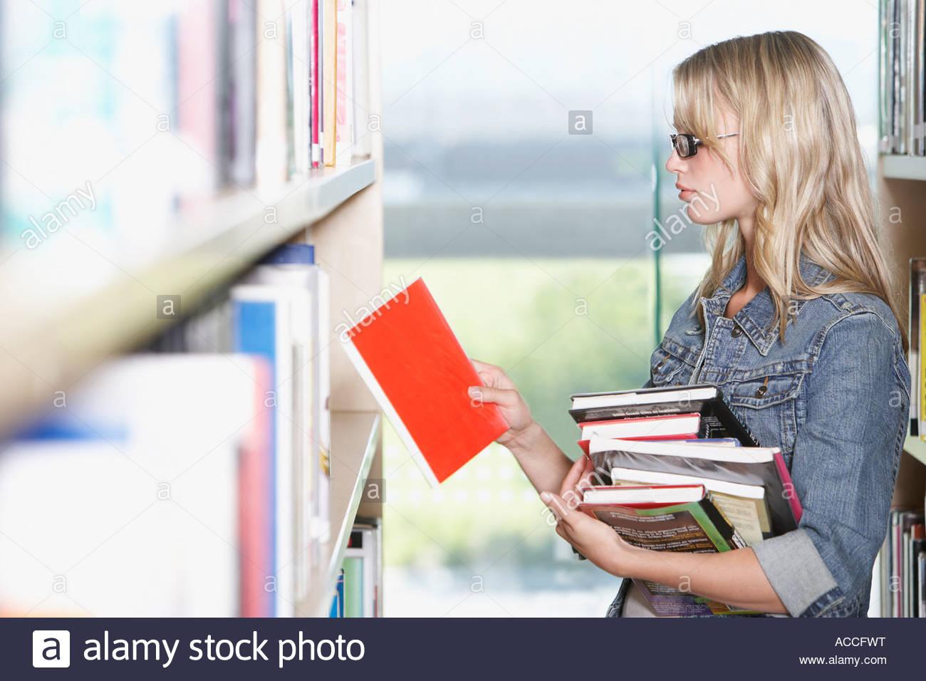Junge Frau in der Bibliothek in der Schule mit Büchern Stockbild