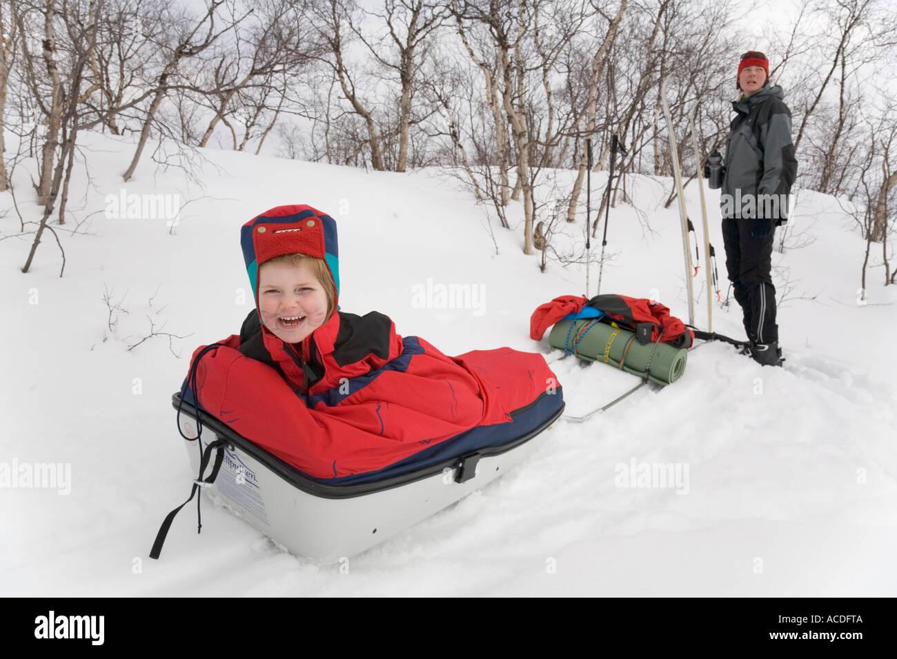 Rodeln in Lappland: eine Mädchen sitzt in eine Pulka, ihre Mutter, die den Schlitten gezogen steht im Hintergrund Stockbild