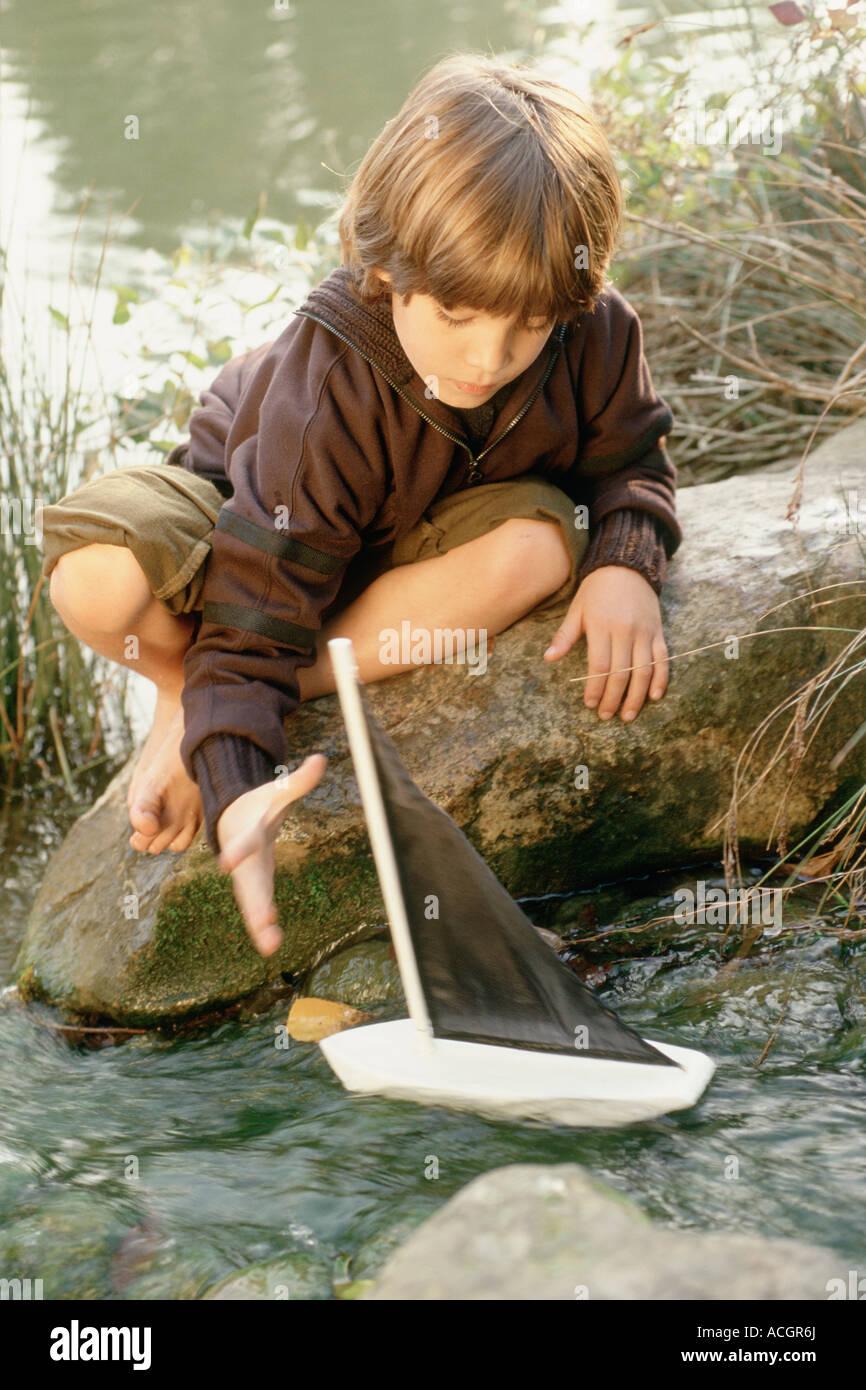 Kleine Junge Sitted am Meer auf einem nackten Füße roch