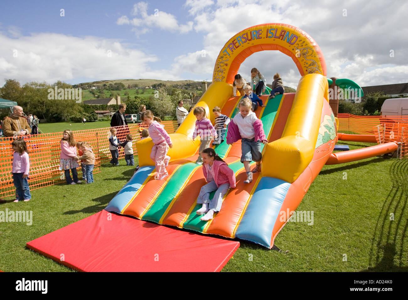 Kinder freuen sich über Hüpfburg und Rutsche auf MayDay fair Woodmancote Gloucestershire UK Stockbild