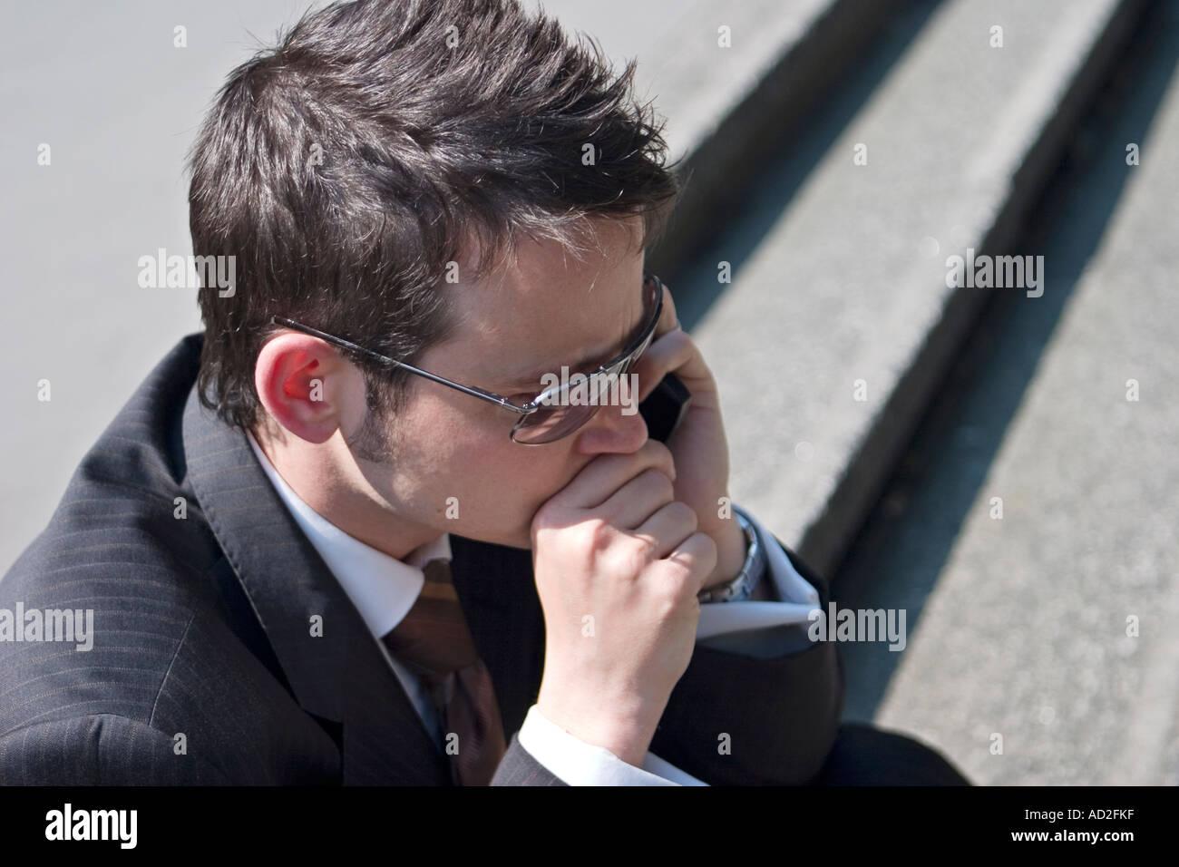 Junger Geschäftsmann legt seine Hand zum Mund, als er in der Londoner City Handy benutzt Stockbild