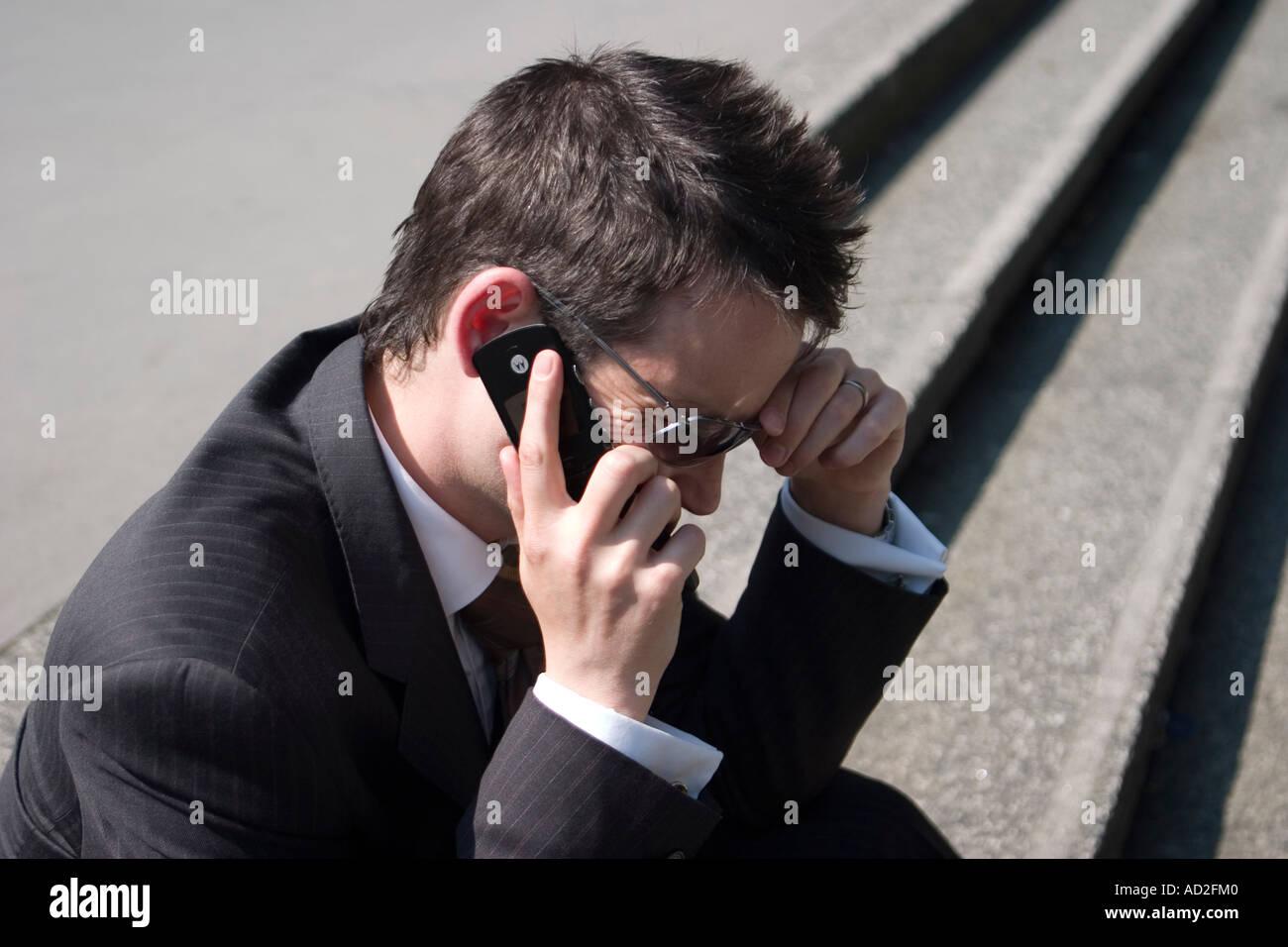 Junger Geschäftsmann legt seine Hand an den Kopf, wie er in der Londoner City Mobiltelefon auf Stufen Stockbild