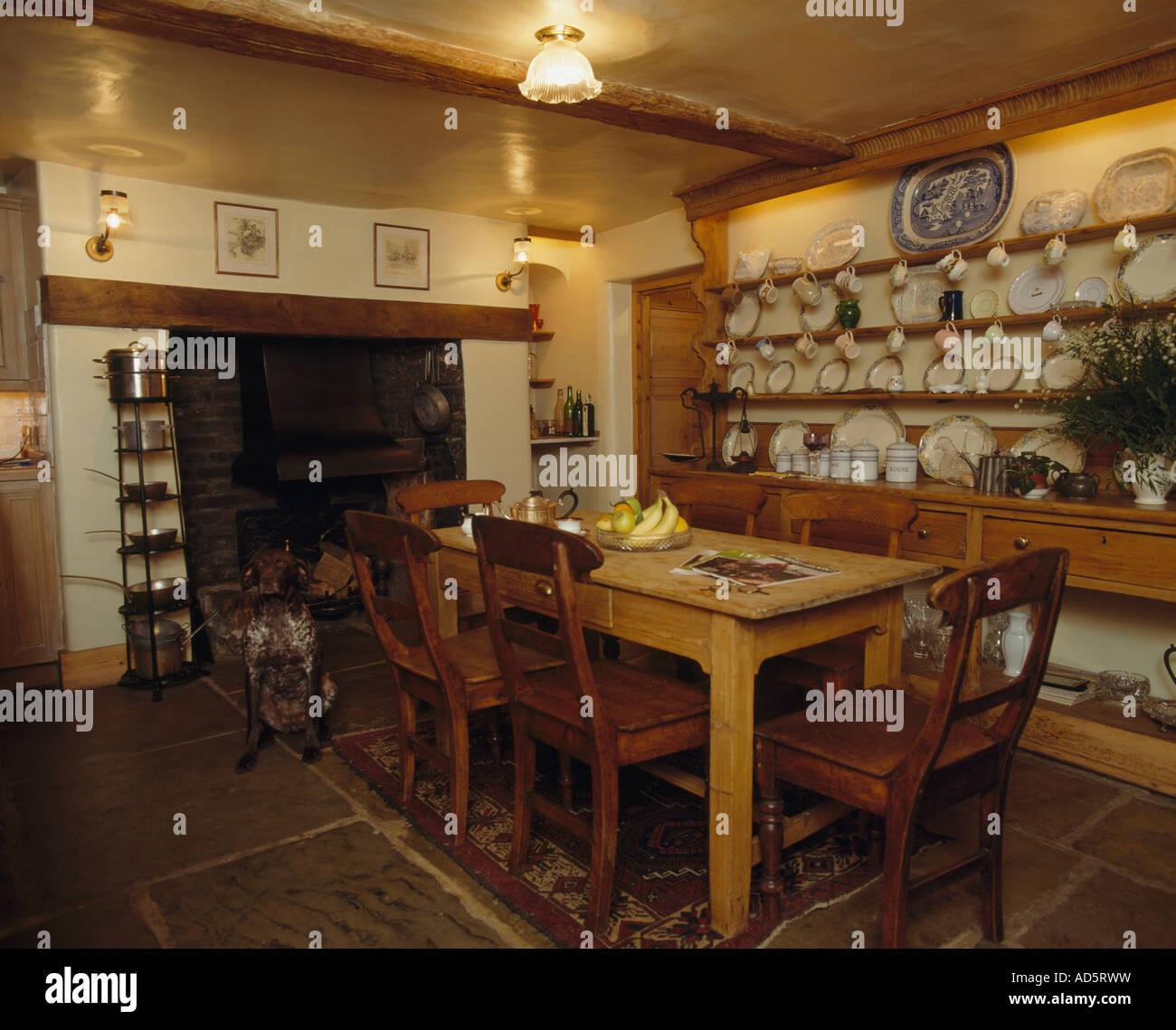 Antike Holzstühle und Tisch im Landhaus-Küche mit Kamin und Platten ...
