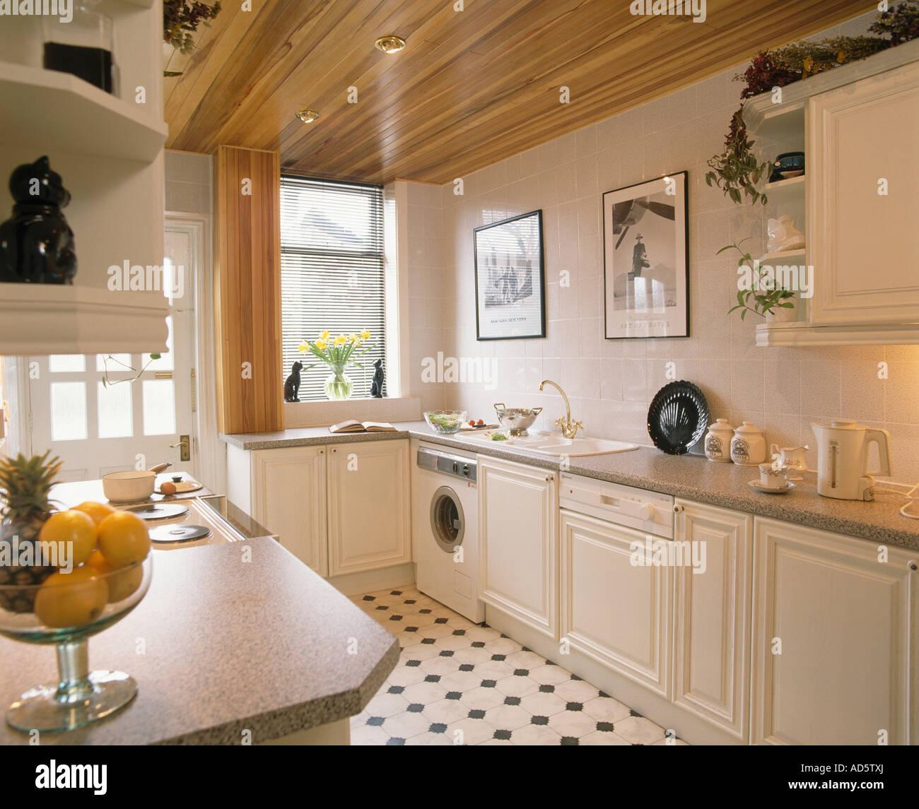 Neutrale Küche mit Holzdecke und eingebauten Geschirrspüler und