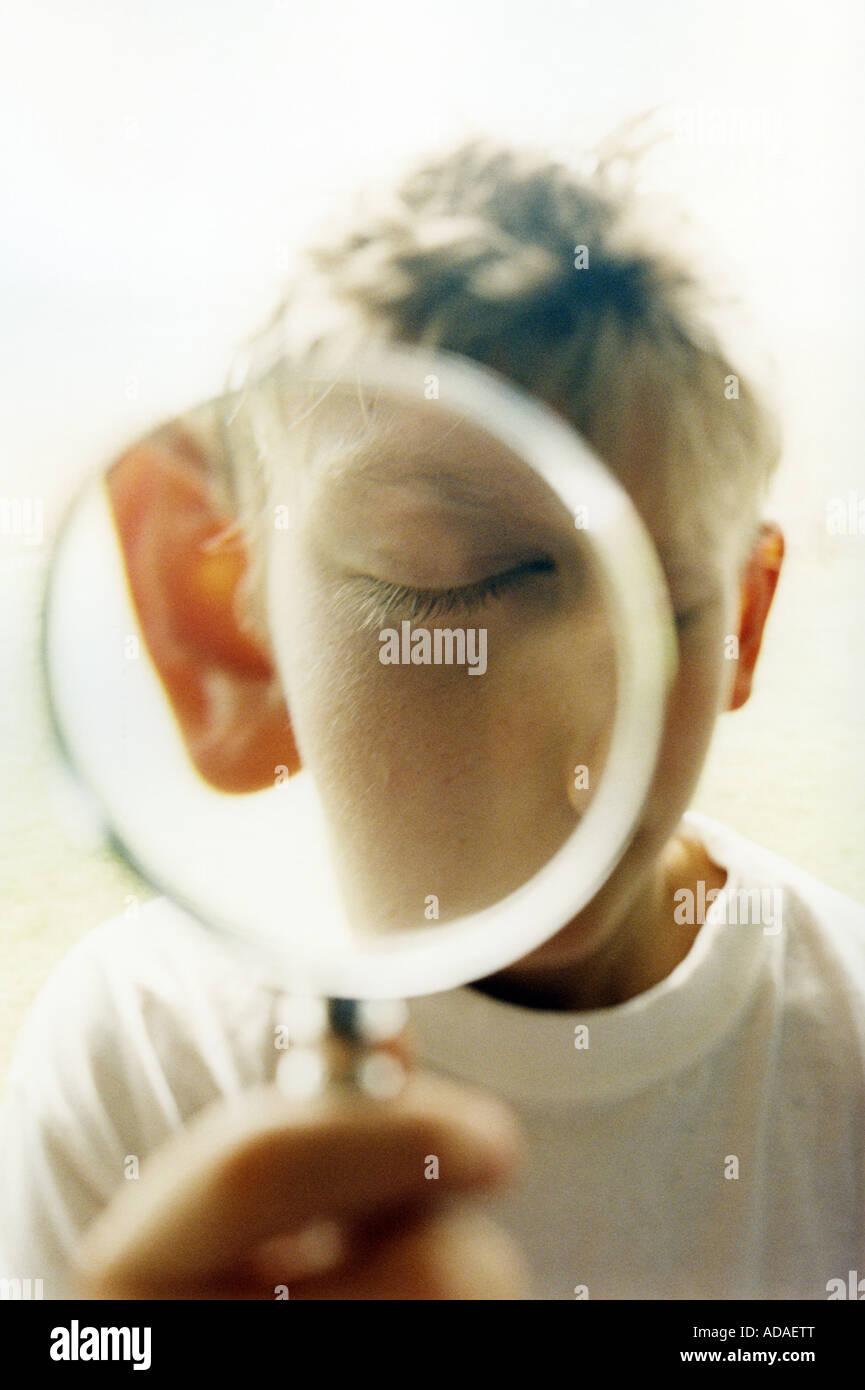ein Junge mit Lupe Stockbild