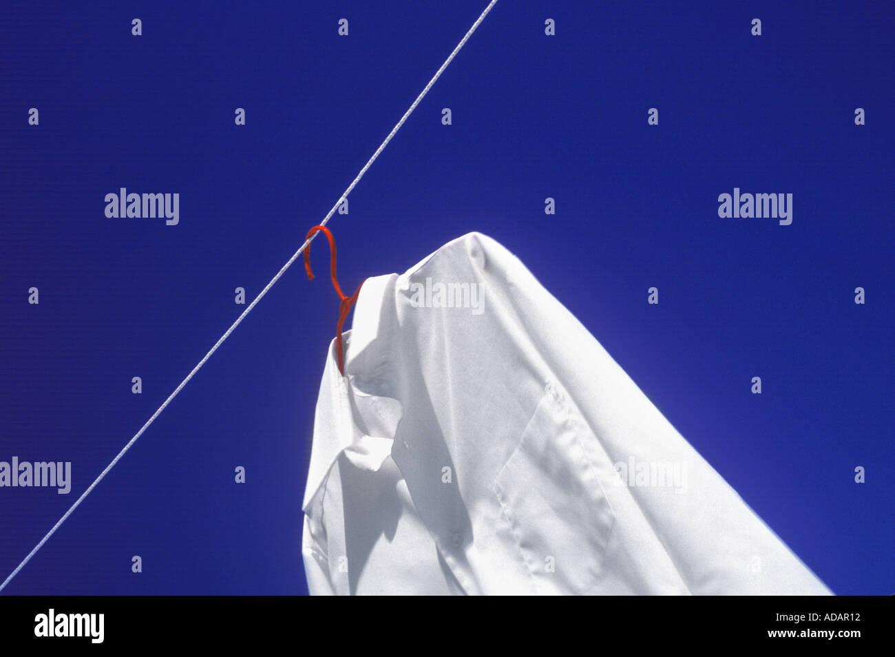 Weißes Hemd und eine rote Bügel auf Wäscheleine mit blauem Himmel Stockbild
