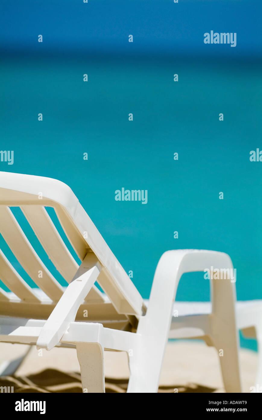 Leere weiße Liegestuhl an einem tropischen Strand mit strahlend blauen Meerwasser Stockbild