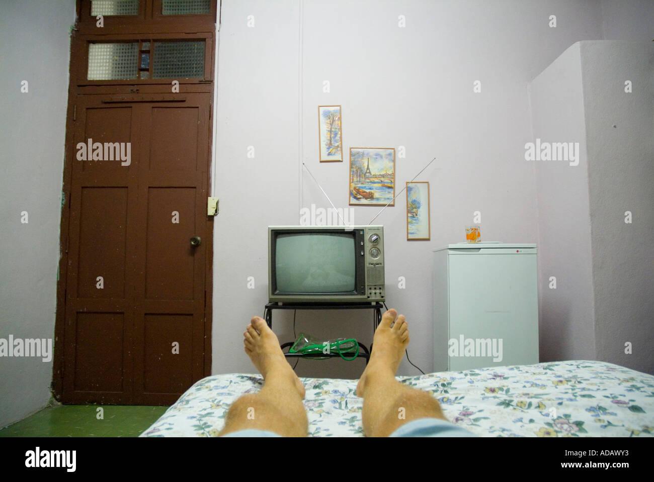 Der Mann Beine auf einem Bett vor einem alten TV in einer Pension / B&B / Hotel/Motel Zimmer Stockbild