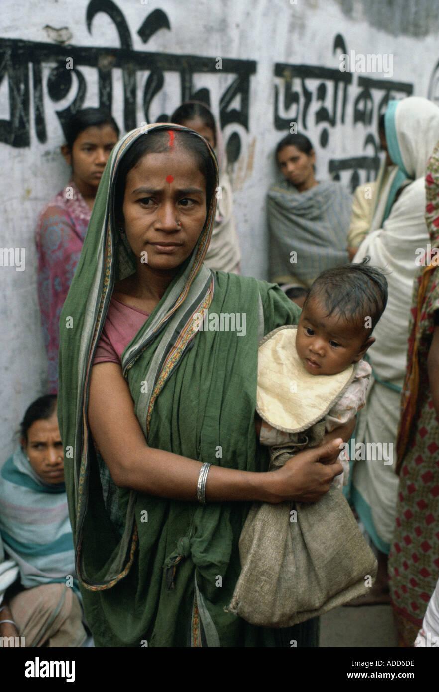 Mutter mit Kind Schlangestehen für Essen mit anderen Frauen bei Mutter Teresa Mission Kalkutta Indien Stockfoto