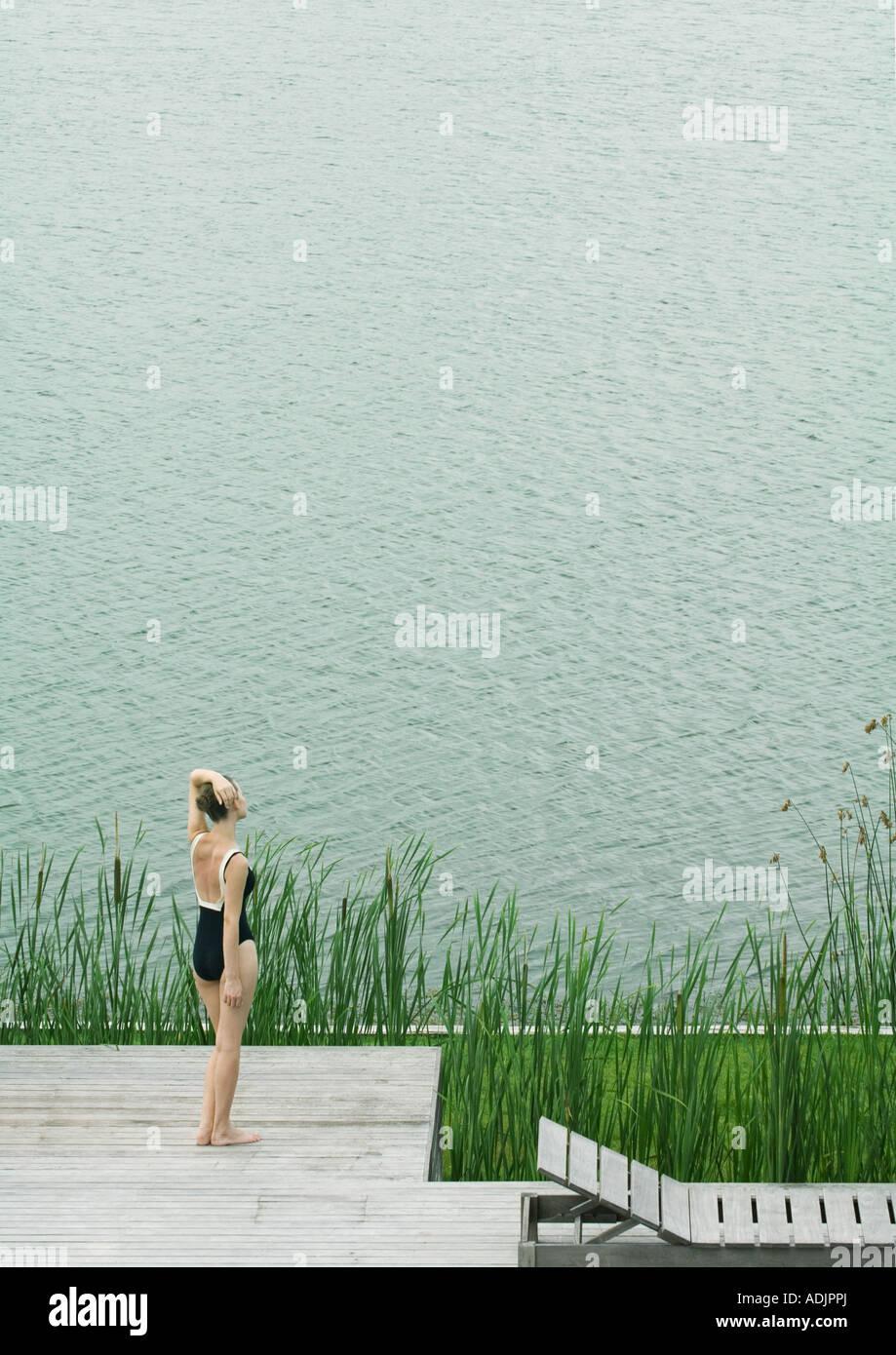 Frau im Badeanzug stehen an Deck, mit Blick auf Gewässer Stockbild