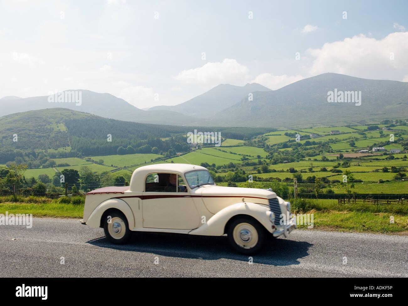 Oldtimer-Tourer auf der Trassey Straße durch die Mourne Mountains, County Down, Irland mit Slieve Bearnagh Stockbild