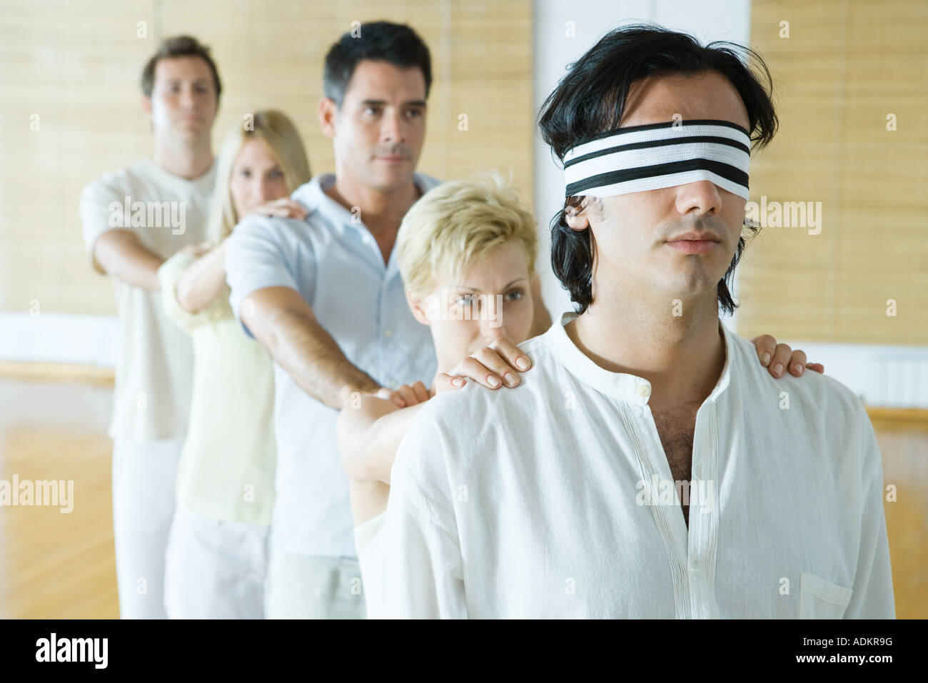 Gruppentherapie, stehend im Gänsemarsch Linie mit den Händen auf die Schultern, Mann mit verbundenen Augen Stockbild