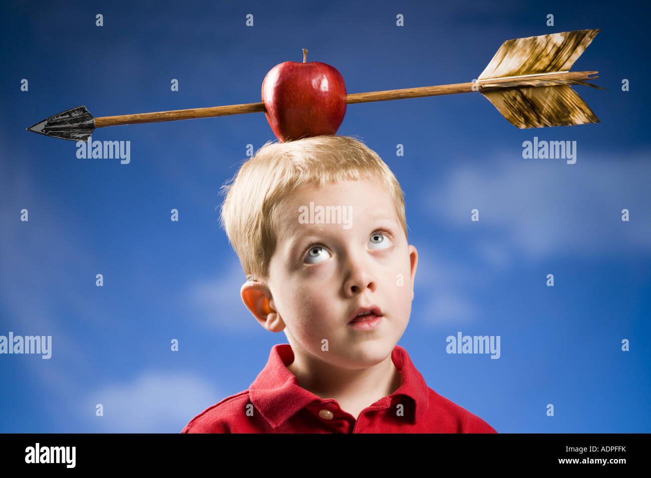 Junge mit Apfel und Pfeil auf Kopf Stockbild