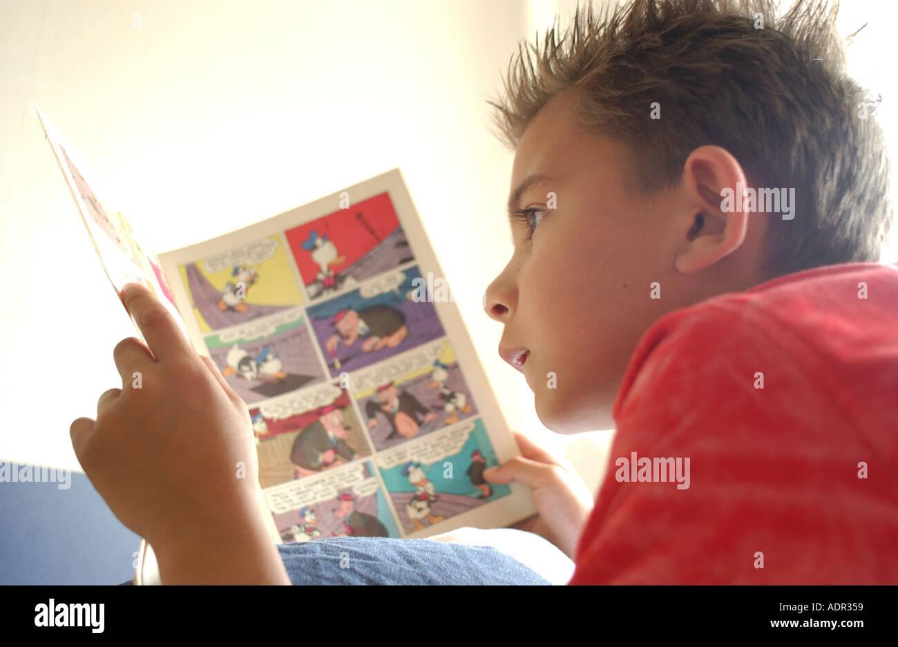 Boy ist ein Comic-Buch auf dem Bauch liegend lesen. Stockbild