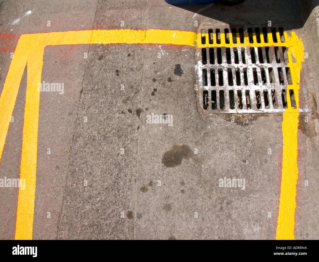 Ein Detail von einem frisch gestrichenen gelbe Straßenmarkierung und einem Abfluss von oben Stockbild