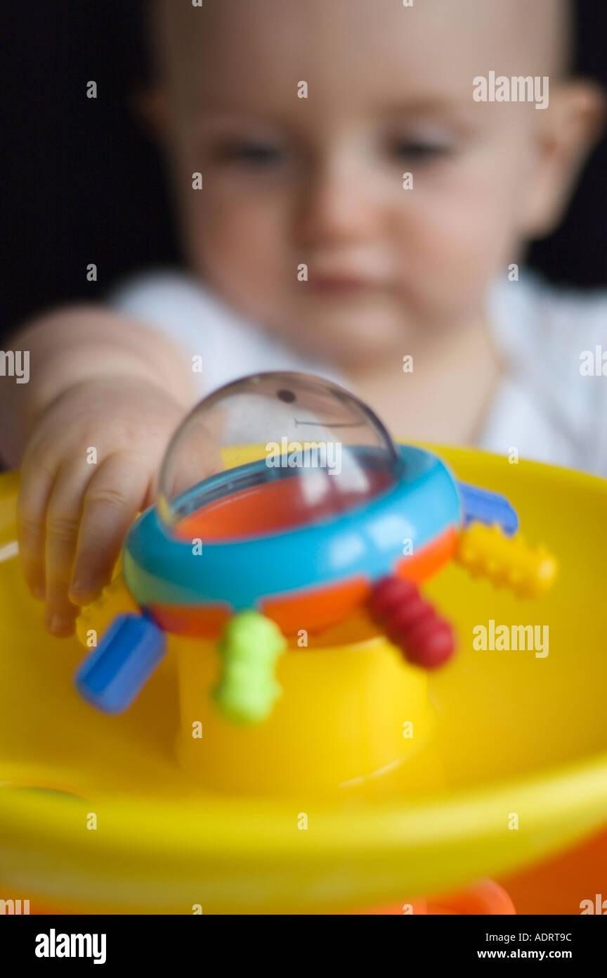 9 Monate altes Baby Boy hält sein Spielzeug Stockfoto