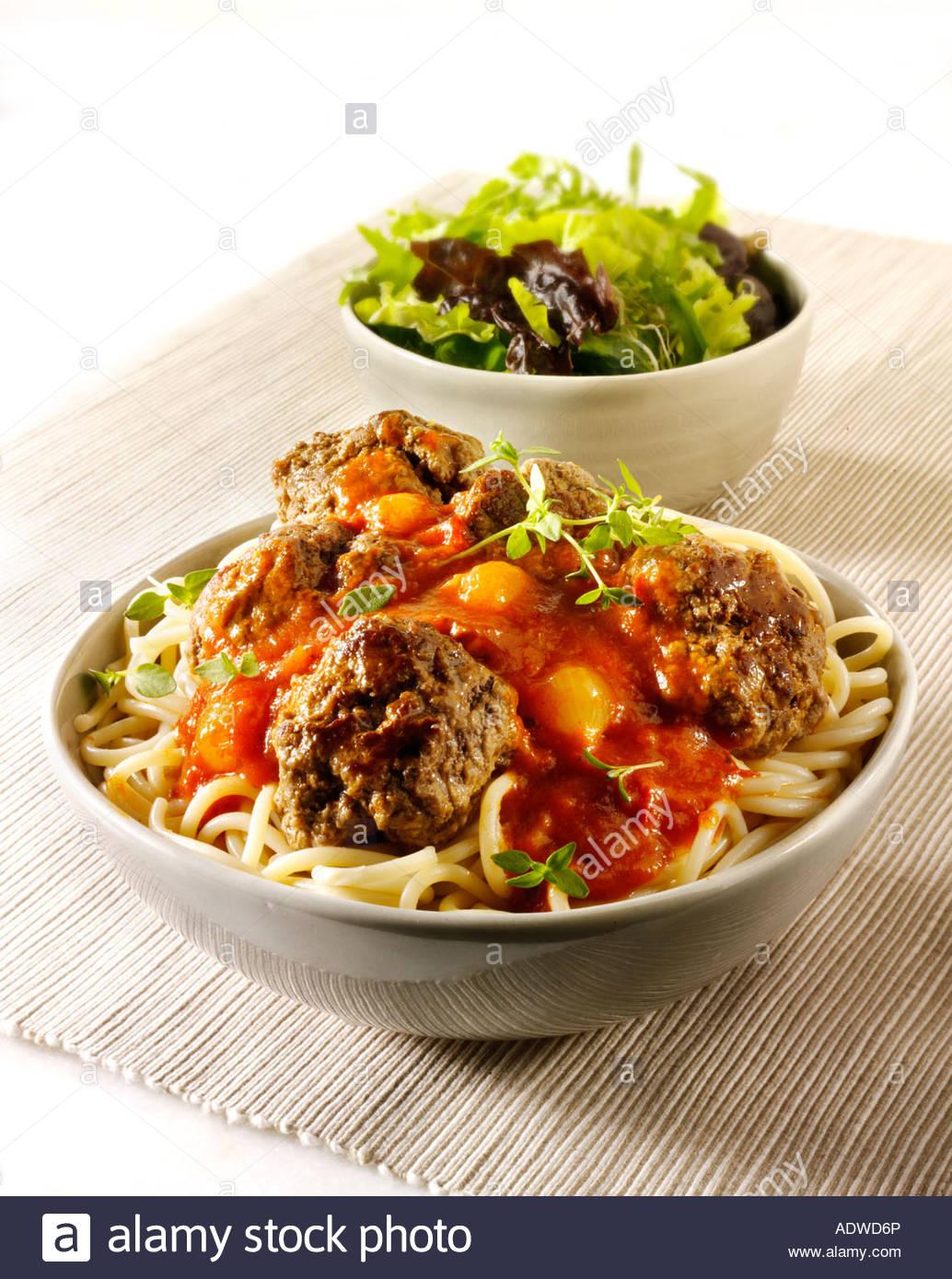 Frikadellen auf Spghetti mit einer Tomatensauce Basilikum Shalott mit einem grünen Salat in eine Tischdekoration Stockbild