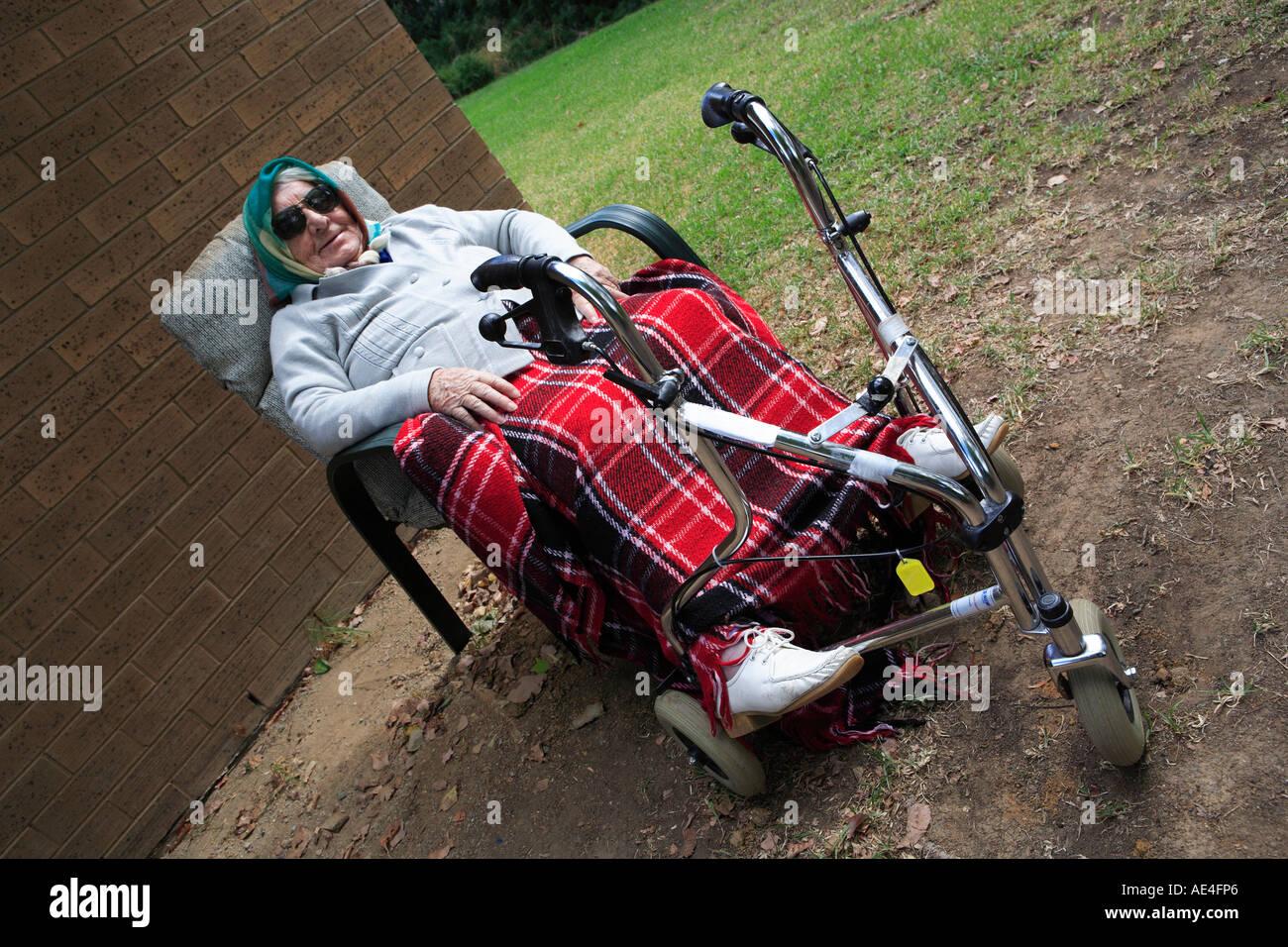 Ältere Dame der neunziger Jahre, draußen zu sitzen, mit Füßen ruht auf ihrer drei-Rad-Gehhilfe Stockbild