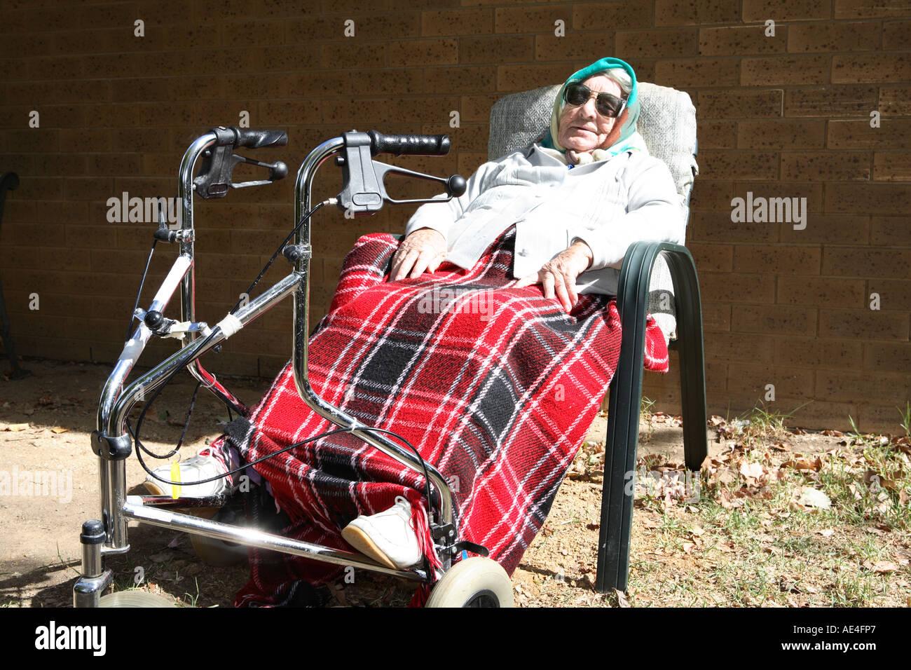 Ältere Dame, die neunziger Jahre draußen mit Füße auf ihr Rad drei walker Stockbild