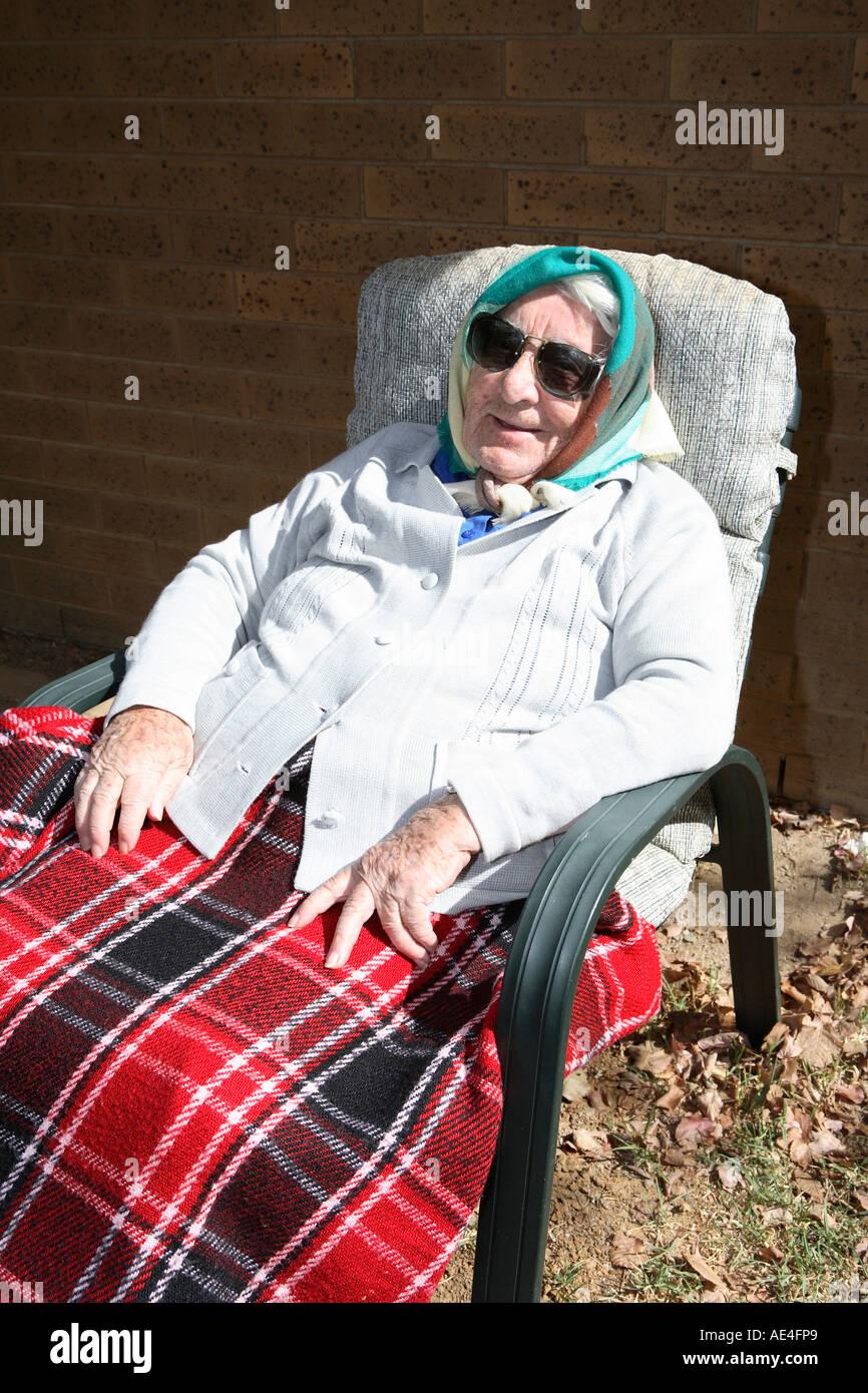 Ältere Dame der neunziger Jahre ruhen draußen Stockbild