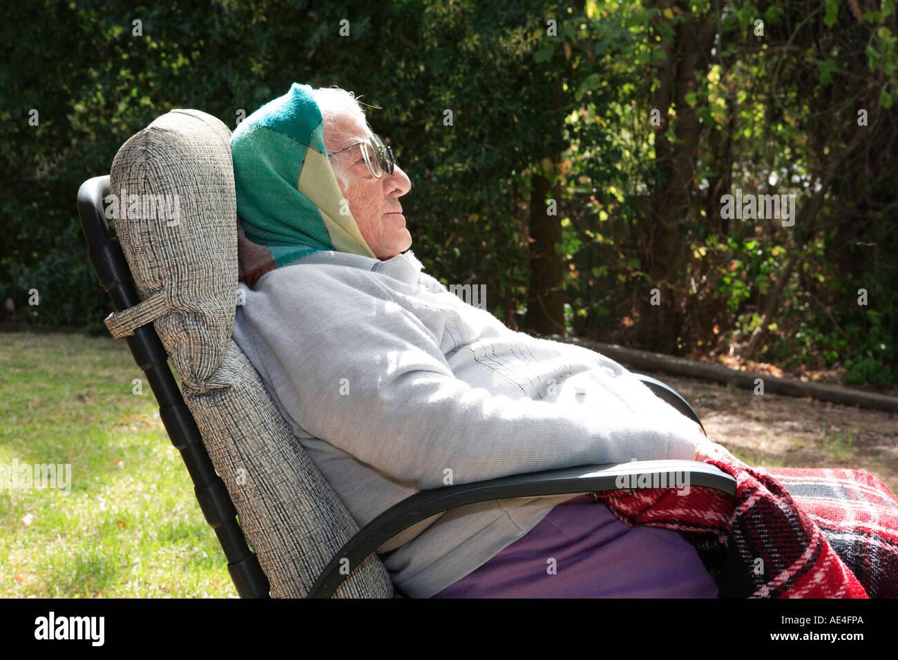 Ältere Dame der neunziger Jahre, draußen ruht in einem Sessel sitzend Stockbild