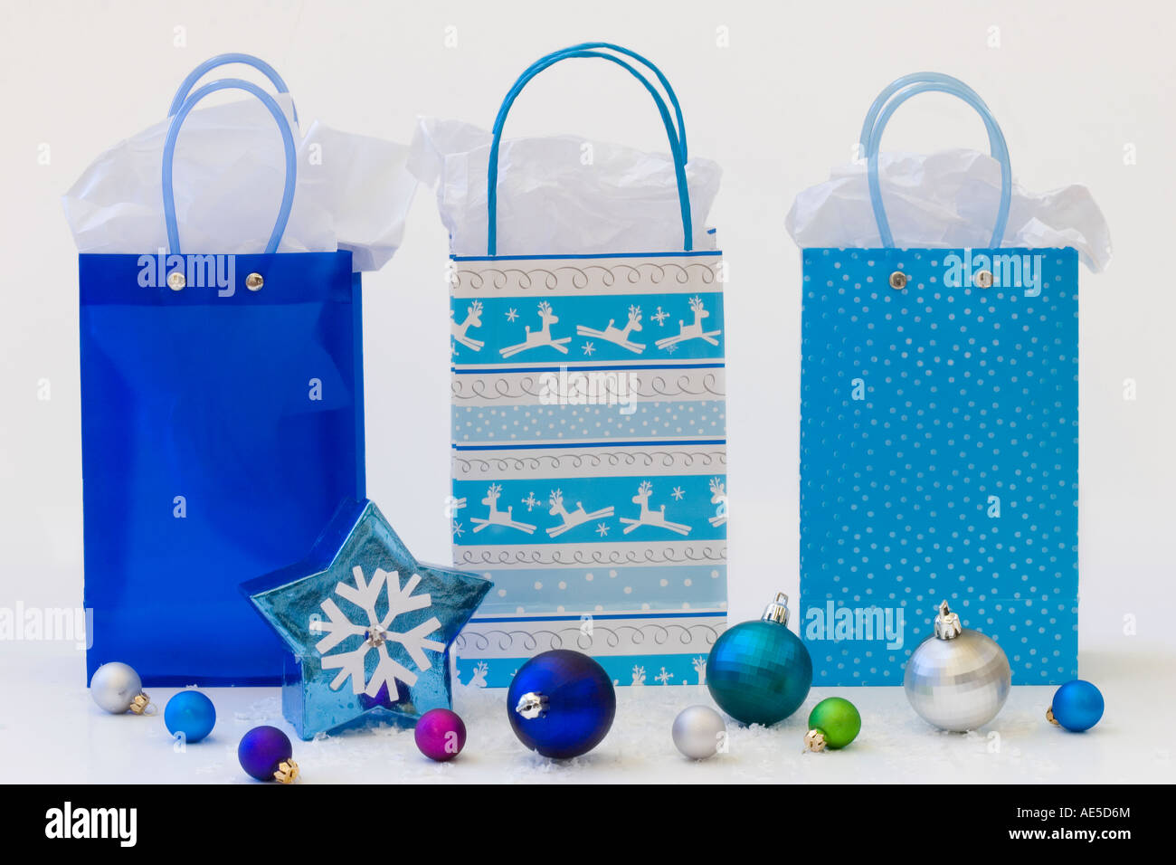 Drei blaue Geschenktaschen mit Seidenpapier und Schneeflocke Stern ...